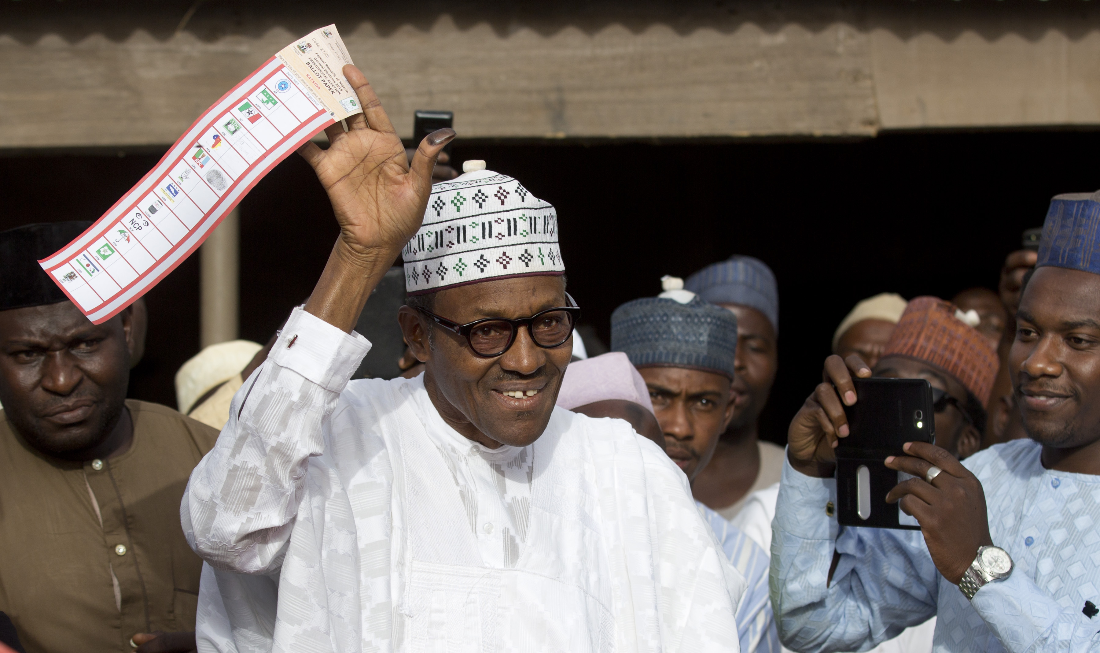 EDS NOTE: ALTERNATIVE CROP OF ABC114. Opposition candidate Gen. Muhammadu Buhari holds his ballot paper in the air before casting his vote in his home town of Daura, northern Nigeria Saturday, March 28, 2015. Nigerians went to the polls Saturday in presidential elections which analysts say will be the most tightly contested in the history of Africa's richest nation and its largest democracy. (AP Photo/Ben Curtis)