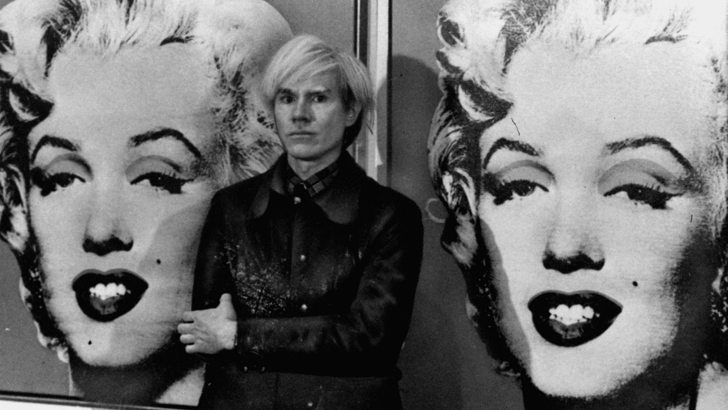 America's pop art painter and filmmaker, Andy Warhol, stands in front of his double portrait of the late Hollywood film star, Marilyn Monroe, at The Tate Gallery in London, February 15, 1971, at a press preview of his exhibition.