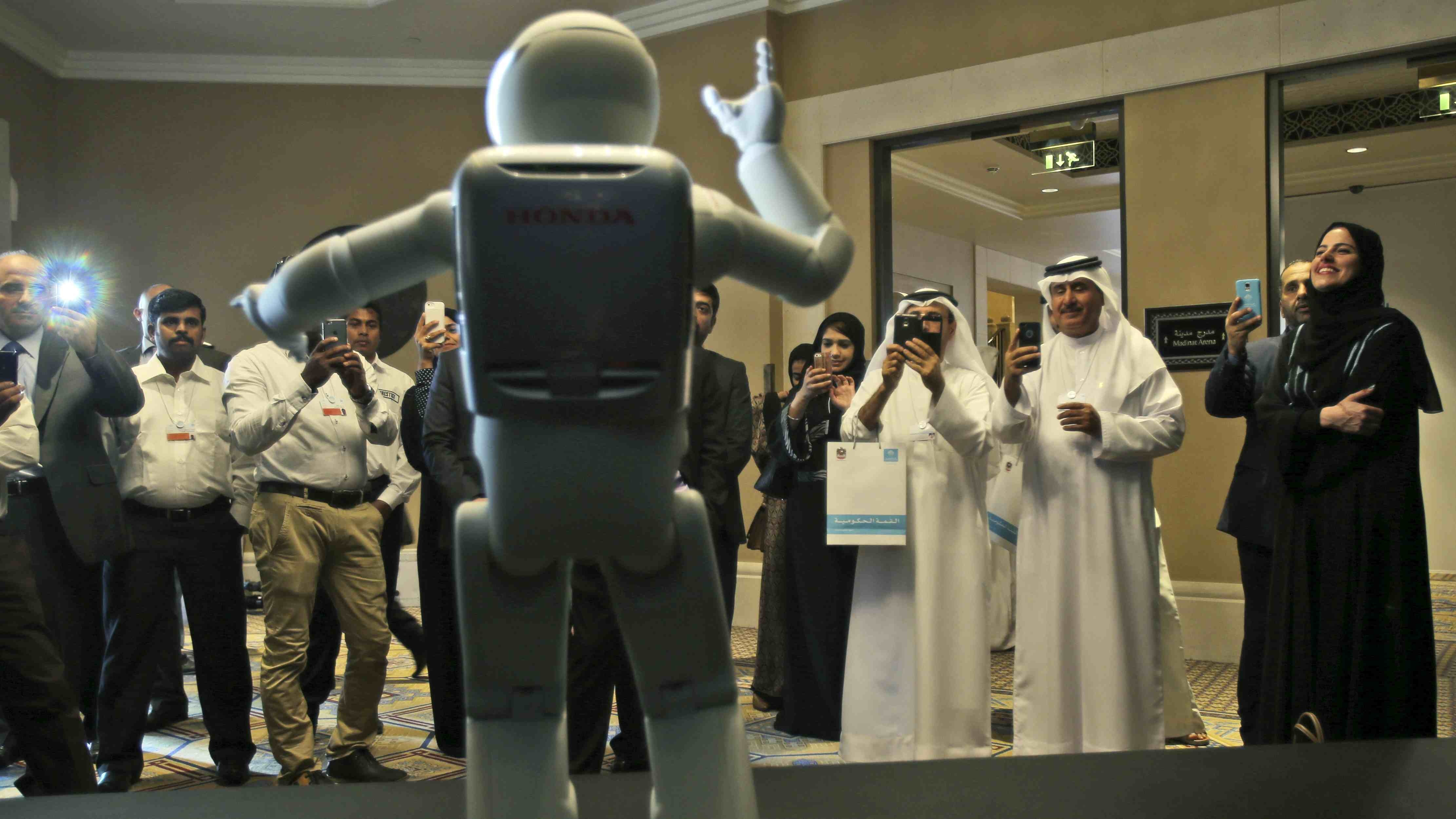 A humanoid robot designed and developed by Honda and named Asimo dances for the audience at the end of the company's  presentation during the last day of the Government Summit in Dubai, United Arab Emirates, Wednesday, Feb. 11, 2015. (AP Photo/Kamran Jebreili)
