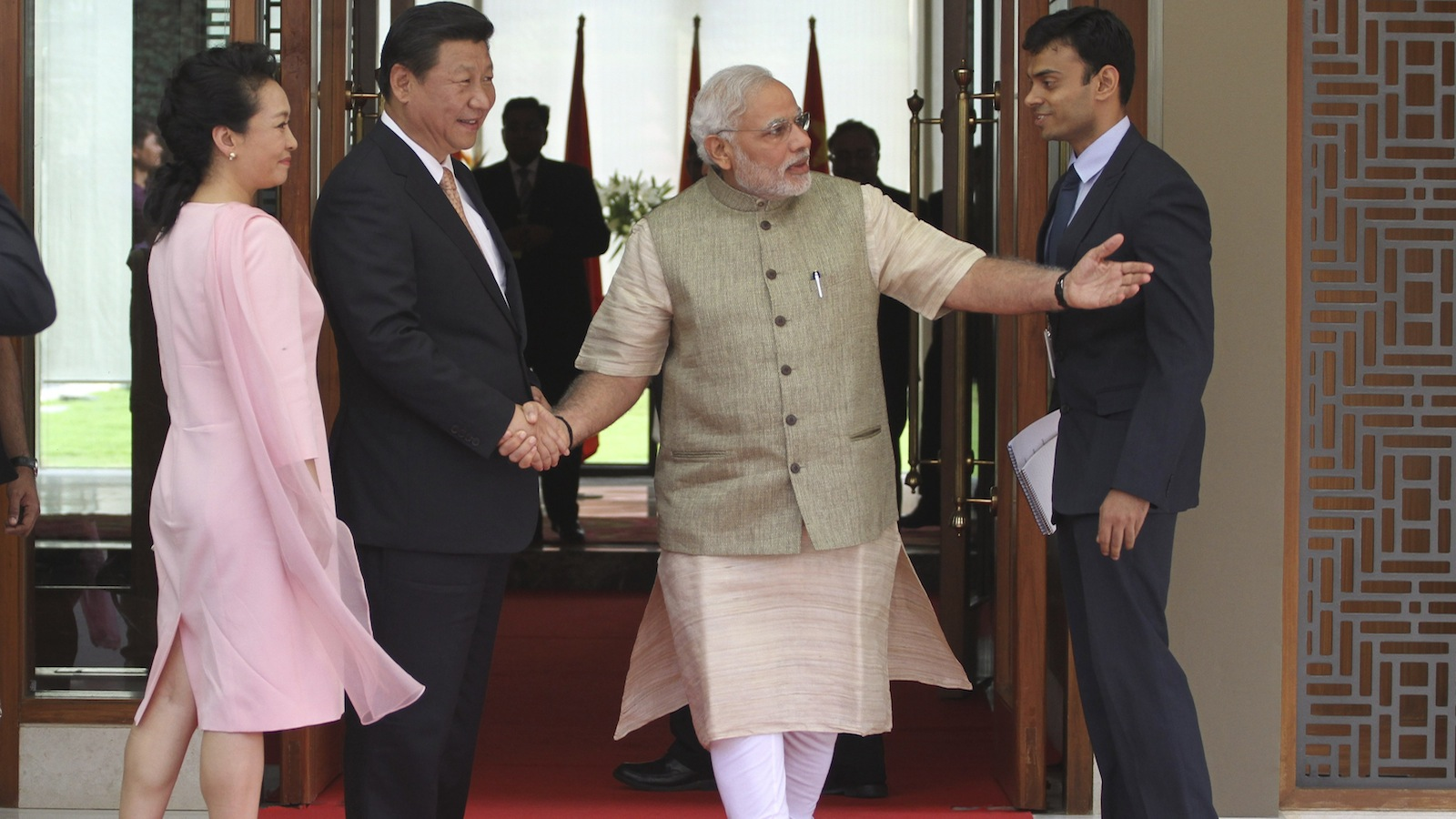 Indian Prime Minister Narendra Modi, center, welcomes Chinese President Xi Jinping, second left and Xi's wife Peng Liyuan, left upon arrival at a hotel in Ahmadabad, India, Wednesday, Sept. 17, 2014. Xi landed in Modi's home state of Gujarat on Wednesday for a three-day visit expected to focus on India's need to improve worn out infrastructure and reduce its trade deficit. (AP Photo/Ajit Solanki)