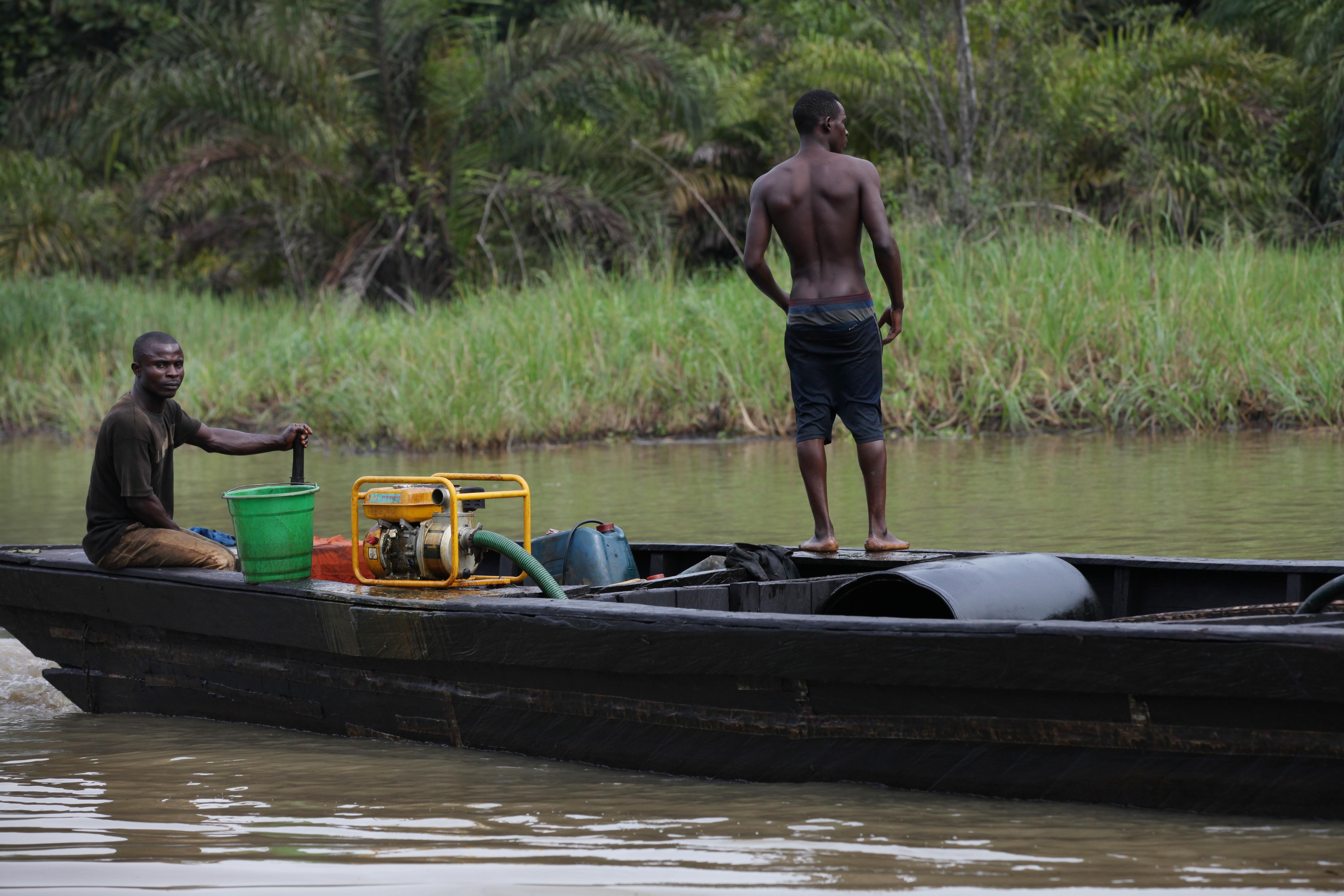suspected oil thieves ride a wooden boat