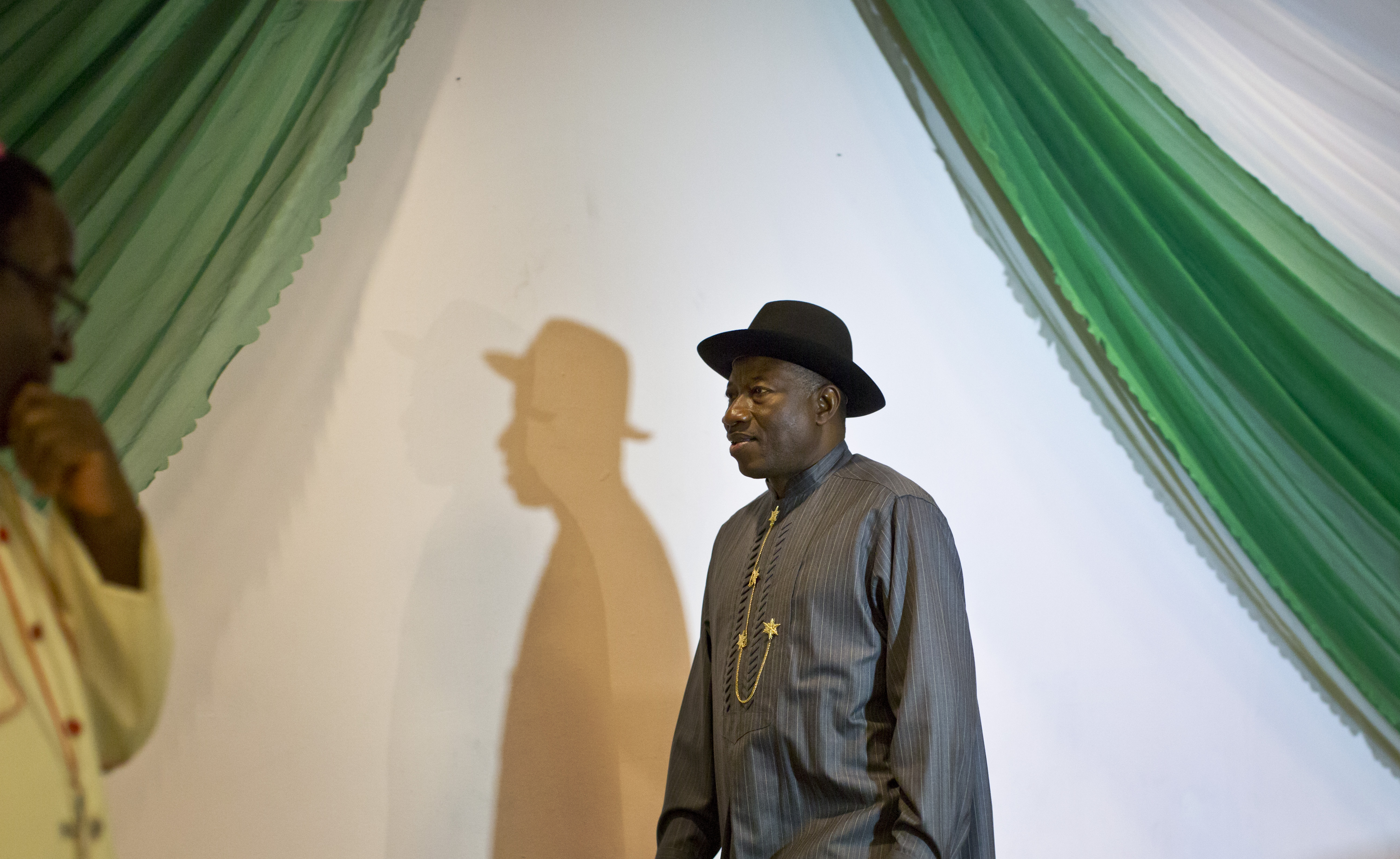 """Nigerian President Goodluck Jonathan, center, arrives on stage to sign a joint renewal with opposition candidate Gen. Muhammadu Buhari of their pledge to hold peaceful """"free, fair, and credible"""" elections, at a hotel in the capital Abuja, Nigeria Thursday, March 26, 2015. Nigerians are due to go to the polls to vote in presidential elections on Saturday. (AP Photo/Ben Curtis)"""