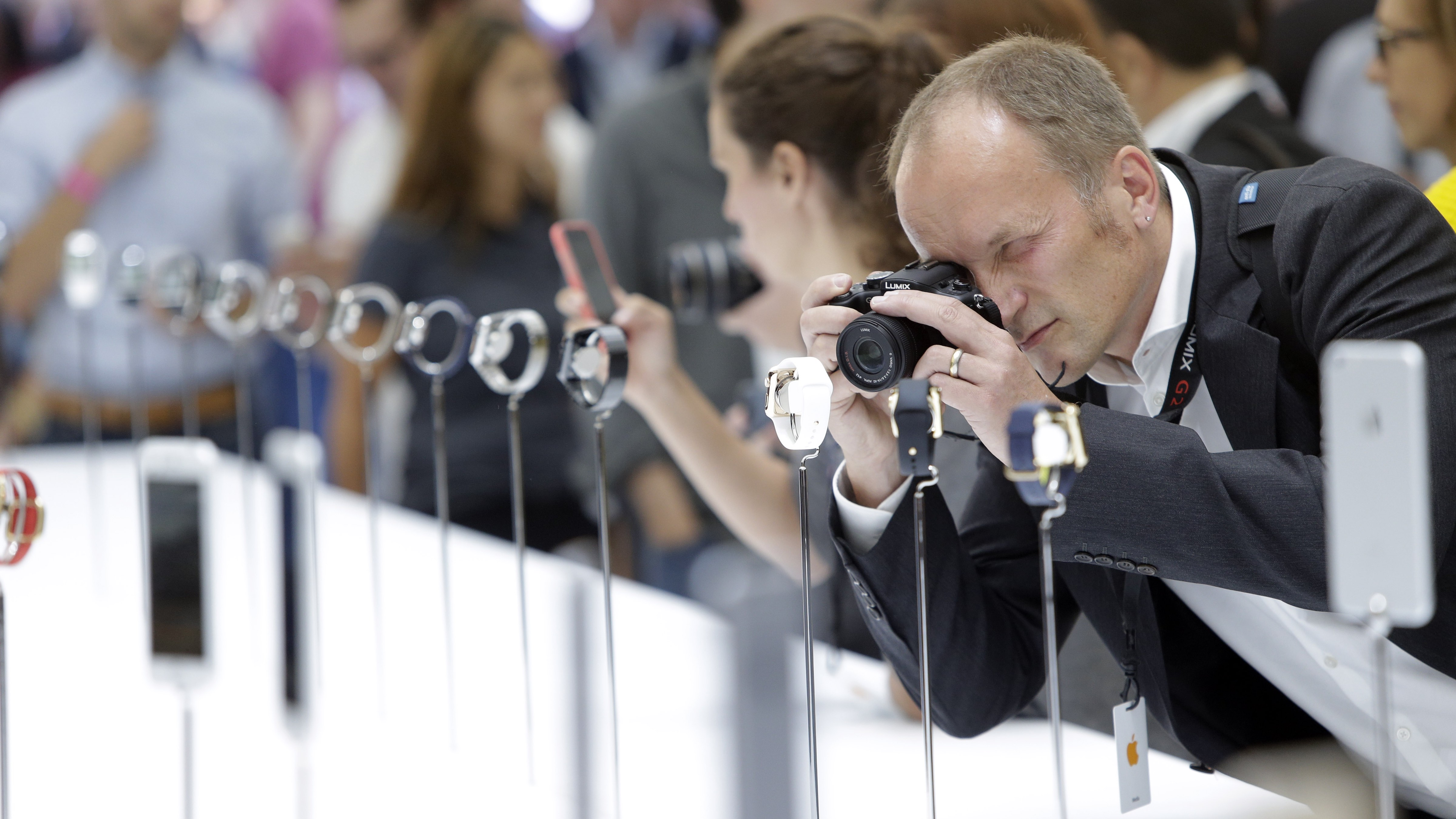 A man photographs Apple Watches during the product release announcement event on Tuesday, Sept. 9, 2014, in Cupertino, Calif. (AP Photo/Marcio Jose Sanchez)