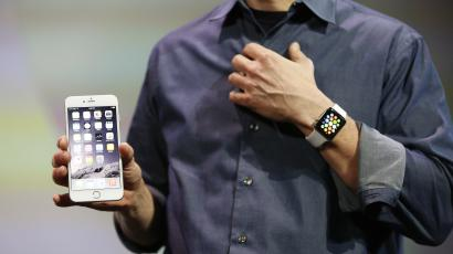 Apple CEO Tim Cook wears the Apple Watch and shows the iPhone 6 Plus during an Apple event at the Flint Center in Cupertino, California, September 9, 2014. REUTERS/Stephen Lam