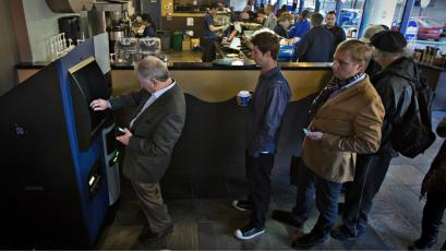Customers line-up to use the world's first ever permanent bitcoin ATM unveiled at a coffee shop in Vancouver, Canada.