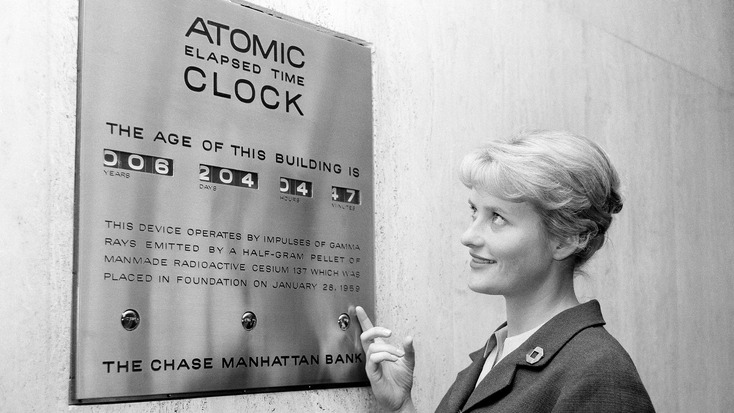 Tour guide Irma Imfeld points out an atomic clock located in the financial section's Chase Manhattan Bank in downtown New York City, Sept. 17, 1963. The clock works on a pellet of Cesium 137. The impulses of gamma rays emitted by the pellet activate the clock which shows the age of the building. The pellet was placed on the foundation of the building when it was built in 1959.