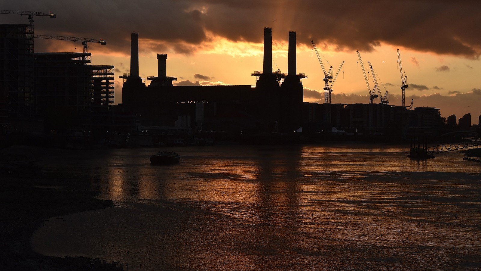 A rig surrounds one (2nd L) of the four chimneys of Battersea Power Station at sunset.