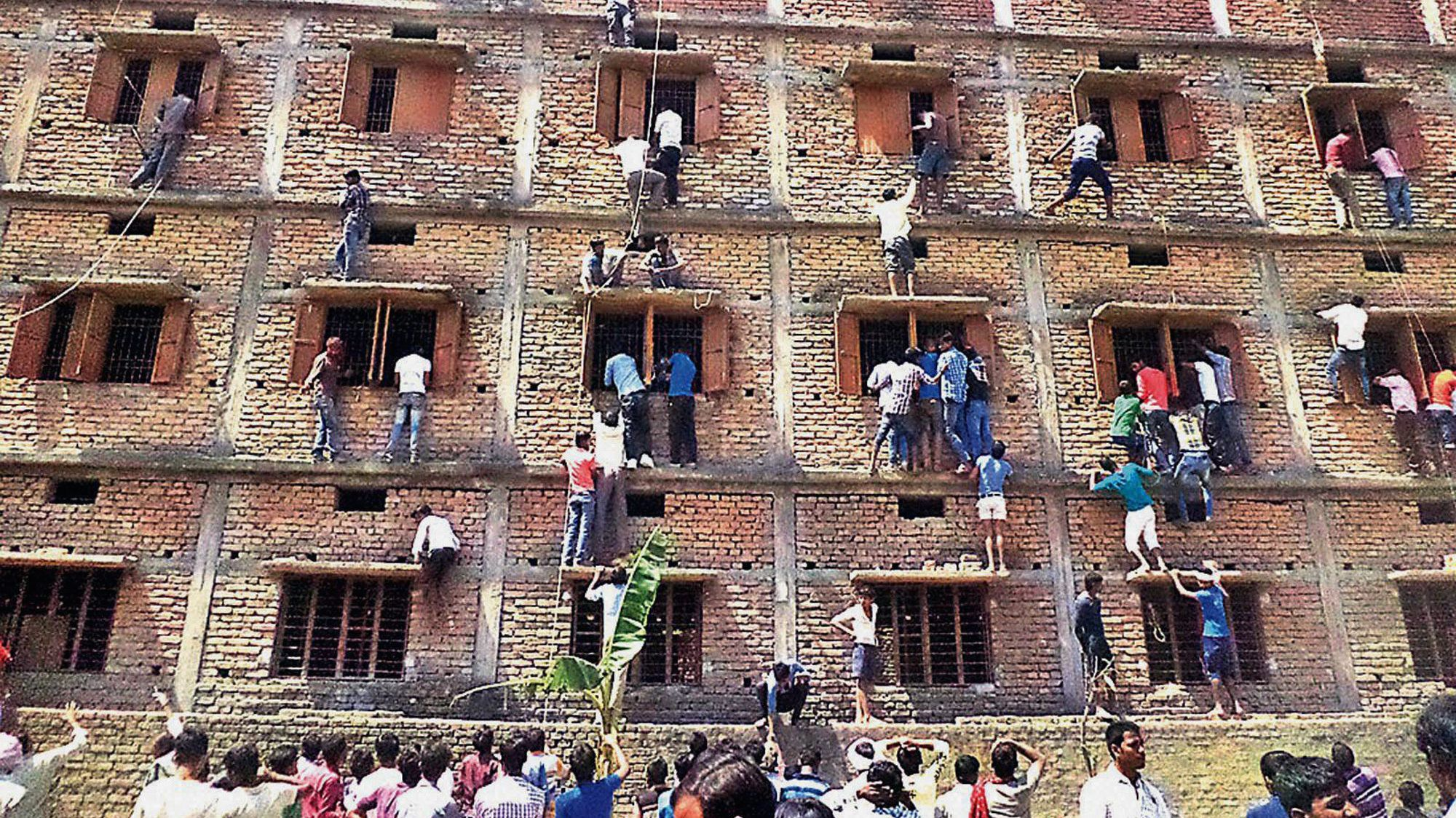 In this Wednesday, March 18, 2015 photo, Indians climb the wall of a building to help students appearing in an examination in Hajipur, in the eastern Indian state of Bihar. Even with police presence, parents and relatives are reported to scale building walls in order to pass notes to help students cheat in their exams. (AP Photo/Press Trust of India)