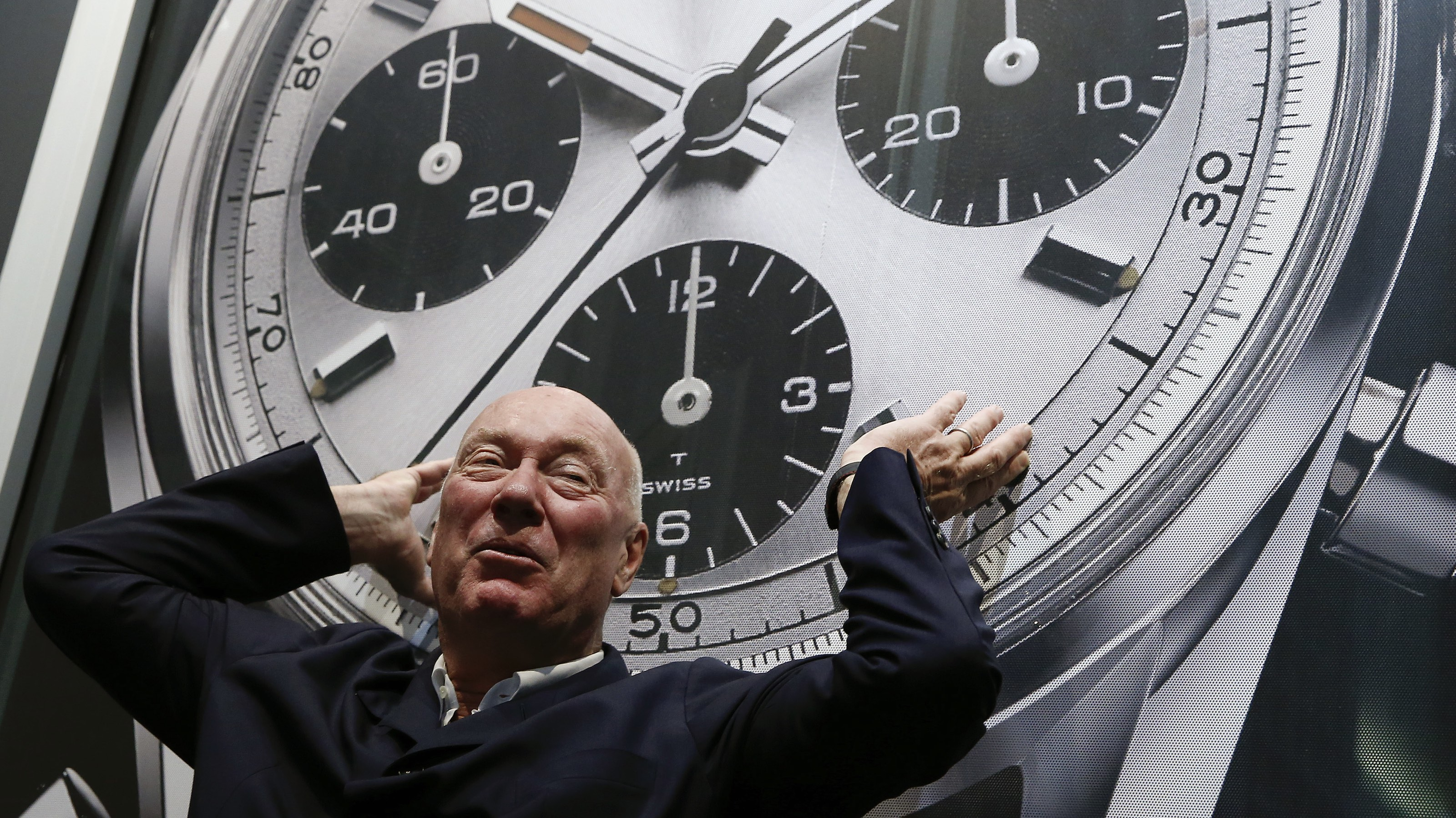 Jean-Claude Biver, head of French luxury goods group LVMH's watch business and interim CEO of the group's biggest watch brand, TAG Heuer, poses in front of an advertising poster before a news conference in the western Swiss town La Chaux-de-Fonds December 16, 2014. REUTERS/Arnd Wiegmann (SWITZERLAND - Tags: BUSINESS)