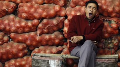 A vendor yawns while waiting for customers at his stall at a vegetable market in Changzhi, Shanxi province September 23, 2008. Less than a quarter of Chinese consumers believe their incomes will rise in the coming three months, according to a quarterly central bank survey released on Monday. REUTERS/Stringer