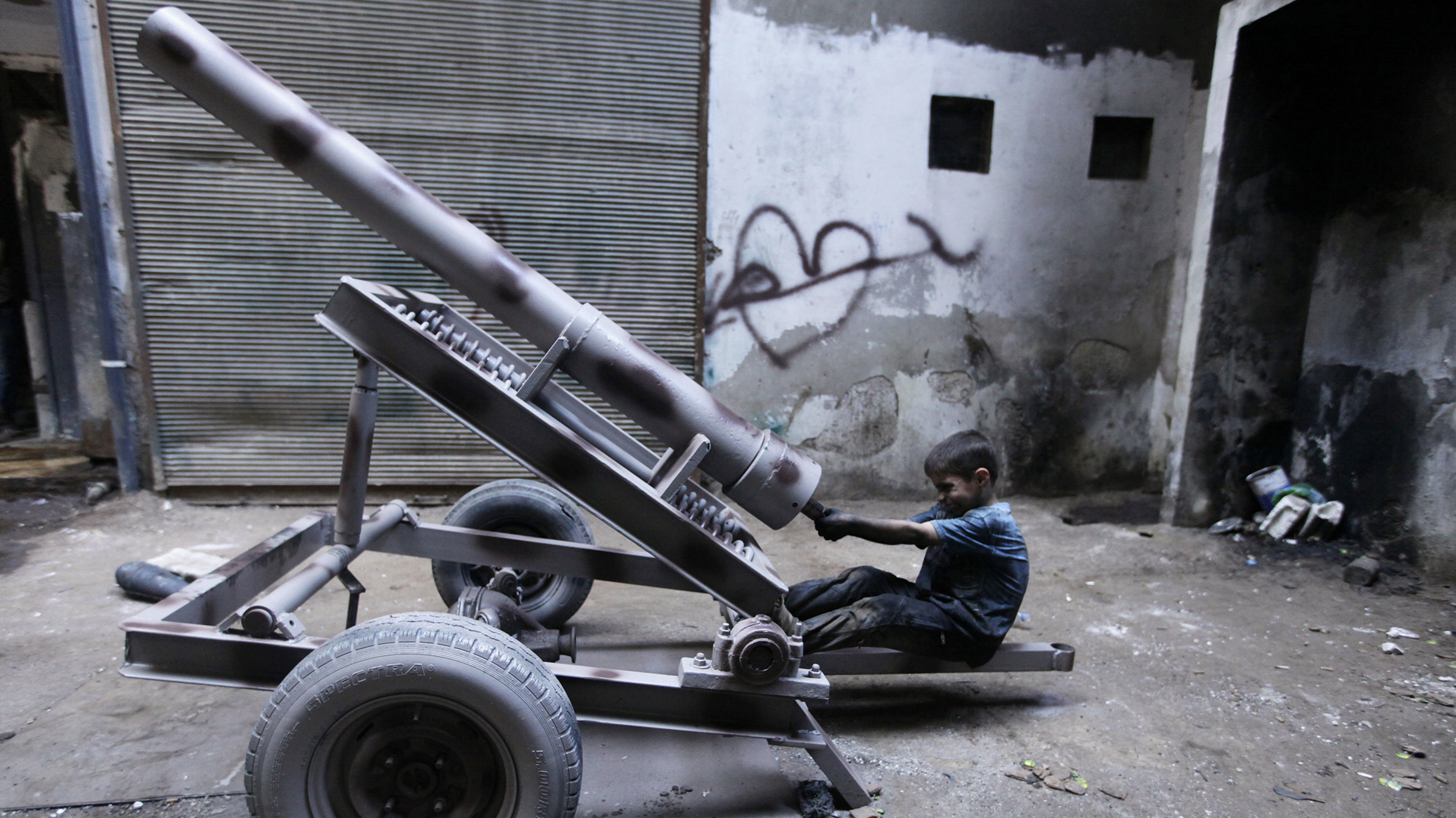 Issa, 10 years old, fixes a mortar launcher in a weapons factory of the Free Syrian Army in Aleppo, September 7, 2013. Issa works with his father in the factory for ten hours every day except on Fridays.