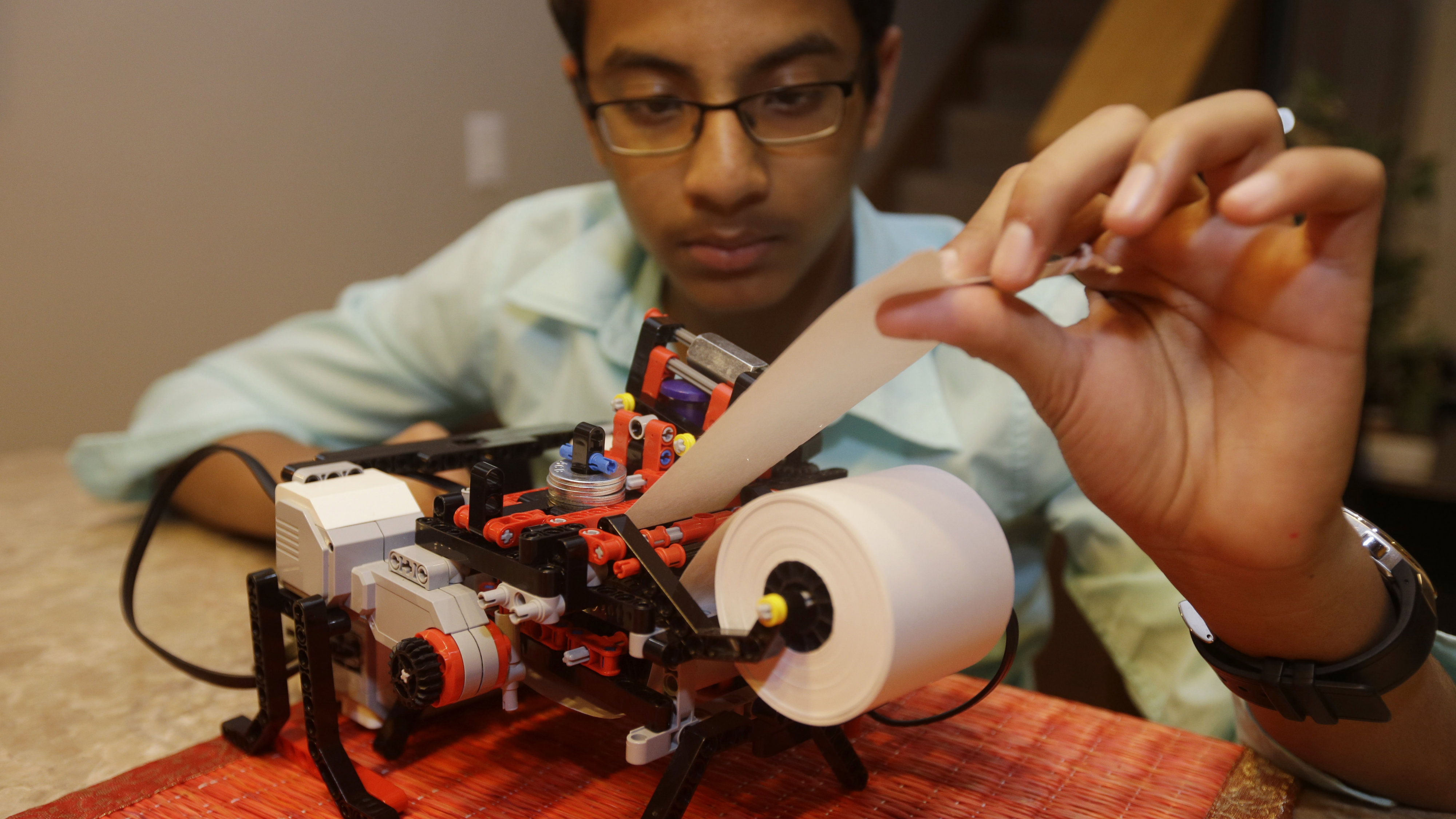 Shubham Banerjee works on his lego robotics braille printer at home Tuesday, Jan. 6, 2015, in Santa Clara, Calif. Banerjee launched a company to develop a low-cost machine to print Braille materials for the blind. It's based on a prototype he built with his Lego robotics kit for a school science fair project. Last month, tech giant Intel Corp. invested in his startup, Braigo Labs, making the 8th grader the youngest entrepreneur to receive venture capital funding.