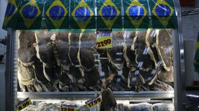 A vendor selling meat arranges his wares next to a display of Brazilian flags in Sao Paulo.