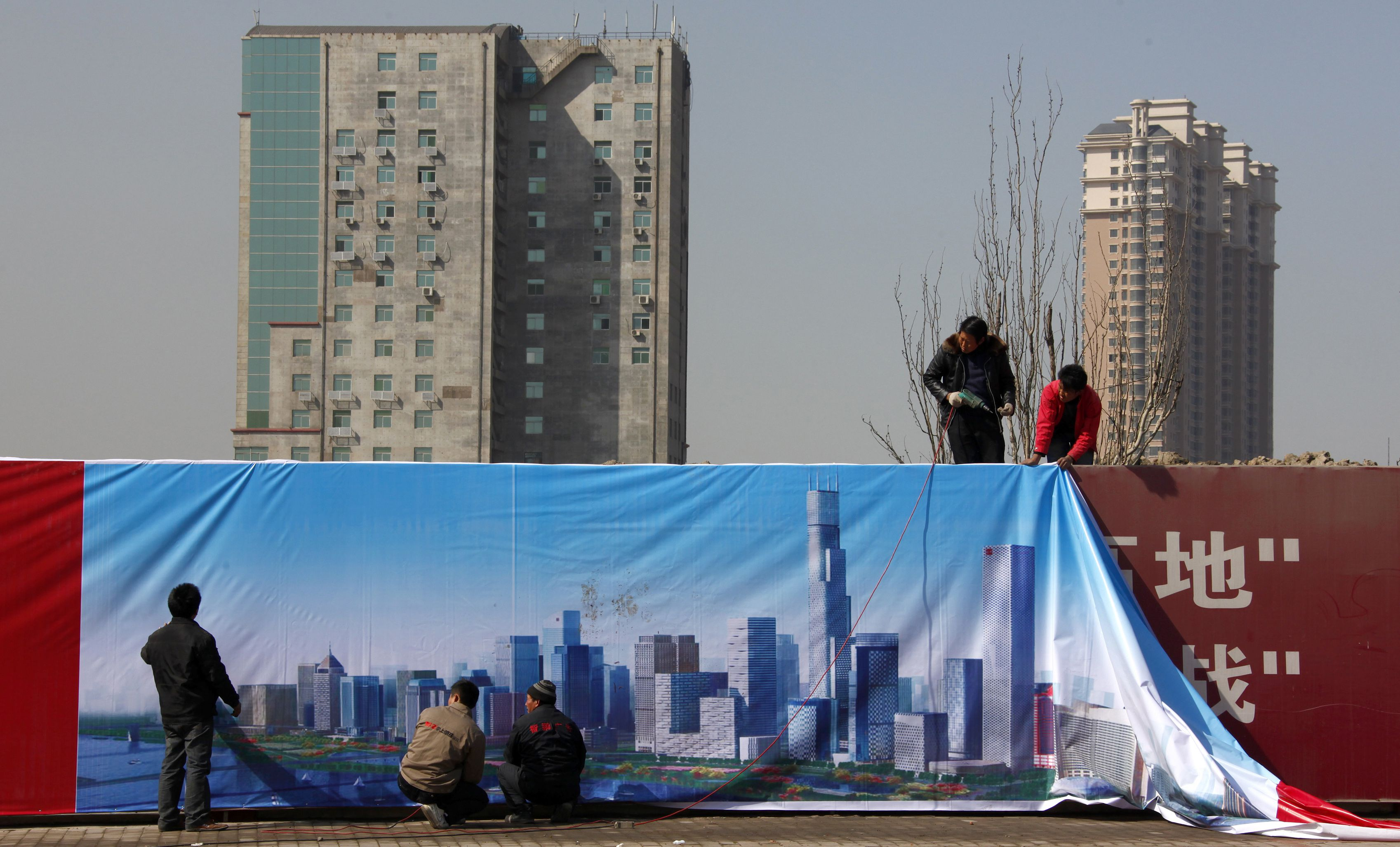 Workmen install a poster onto a wall surrounding a construction site showing an artist's impression of the new business district of Binhai, located in the Yujiapu financial zone on the outskirts of the city of Tianjin March 2, 2011. Round-the-clock construction is transforming muddy ground into what officials boast will be the world?s largest financial zone, a monument to the ambitions that have driven China to dizzyingly fast growth. When the country?s leaders gather for their annual parliament in Beijing on Saturday, they will endorse plans to tap the brakes on the speeding economy, a shift that is needed to keep inflation and debt, under control for now, from becoming far more troublesome. But they need only make the one-hour trip to the financial district sprouting up in Tianjin to see how hard-driving local officials, cash-rich state-owned banks and the soaring aspirations of people seeking a better life are imperiling their designs for slower, steadier growth. REUTERS/David Gray