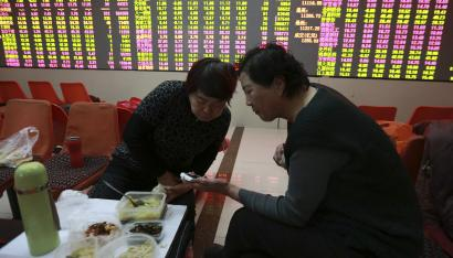 DATE IMPORTED:Investors look at a mobile phone as they have lunch in front of an electronic board showing stock information at a brokerage house in Shenyang, Liaoning province February 5, 2015. China stocks surrendered early gains on Thursday as traders took profits after the central bank unveiled its latest stimulus measures. REUTERS/Stringer (CHINA - Tags: BUSINESS) CHINA OUT. NO COMMERCIAL OR EDITORIAL SALES IN CHINA