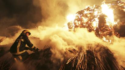 A firefighter attempts to extinguish a fire which broke out on piles of reed at a paper factory in Changde, Hunan province February 16, 2014. No casualty was reported, according to local media. Picture taken February 16, 2014.
