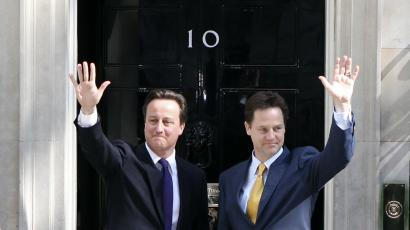 Britain's Prime Minister David Cameron (L) and Deputy Prime Minister Nick Clegg wave on the steps of 10 Downing Street.