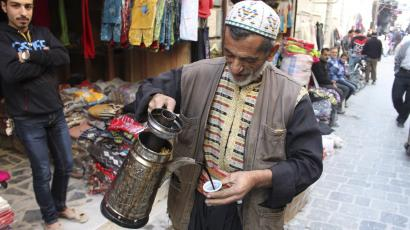 A coffee vendor pours a cup of coffee in Old Aleppo.