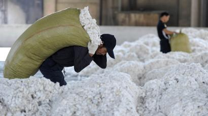 A worker carries a sack of cotton at a cotton purchasing station in China's Anhui province.