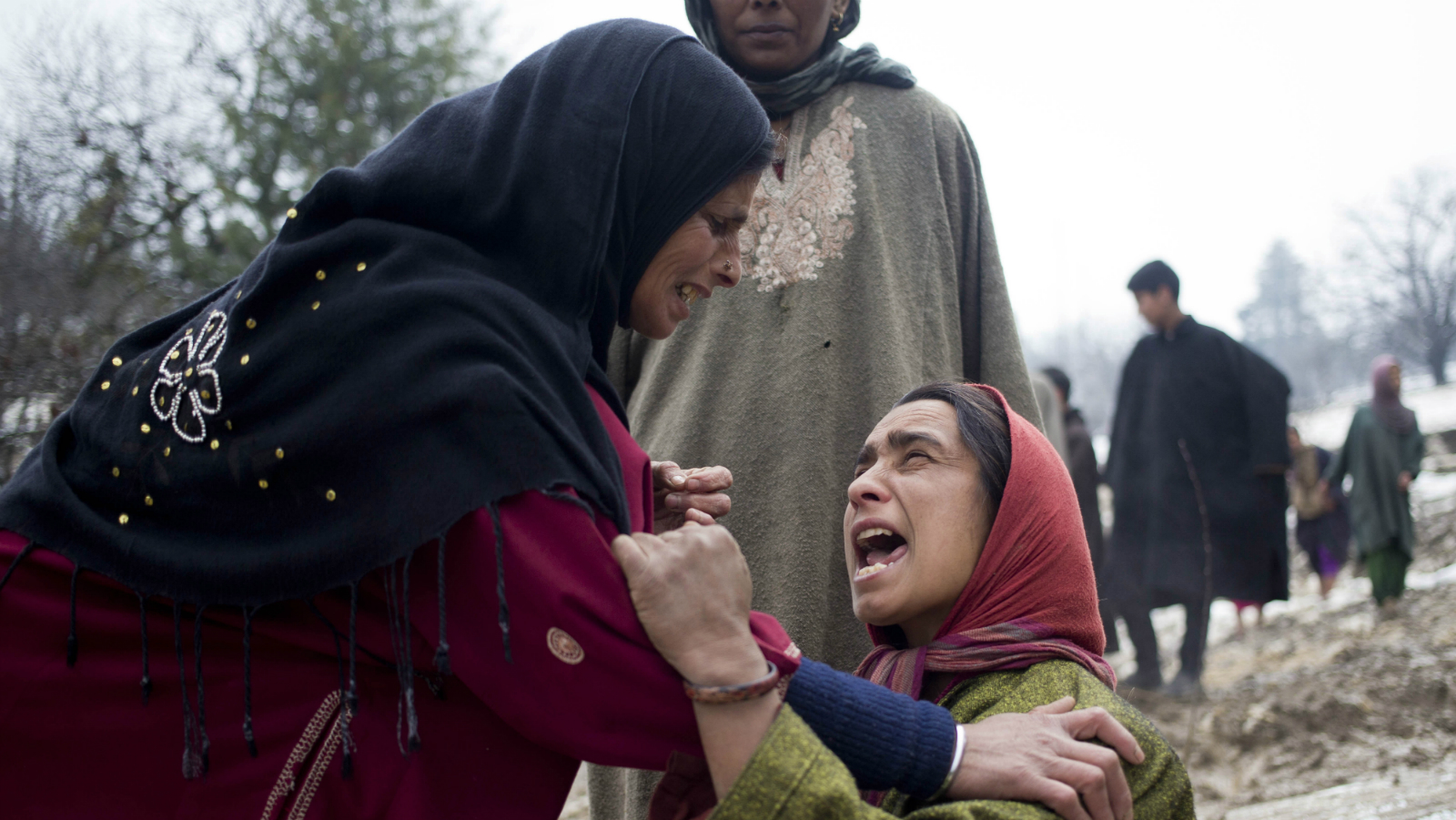 An unidentified woman, left, comforts a relative of landslide victims in village of Laden some 45 Kilometers (28 miles) west of Srinagar, Indian-controlled Kashmir, Monday, March 30, 2015. Hundreds of Kashmiris in both India and Pakistan moved to higher ground Monday as rain-swollen rivers swamped parts of the disputed Himalayan region placed under an emergency flood alert just six months after some 600 people died in flooding that left the region in shambles. (AP Photo/Dar Yasin)