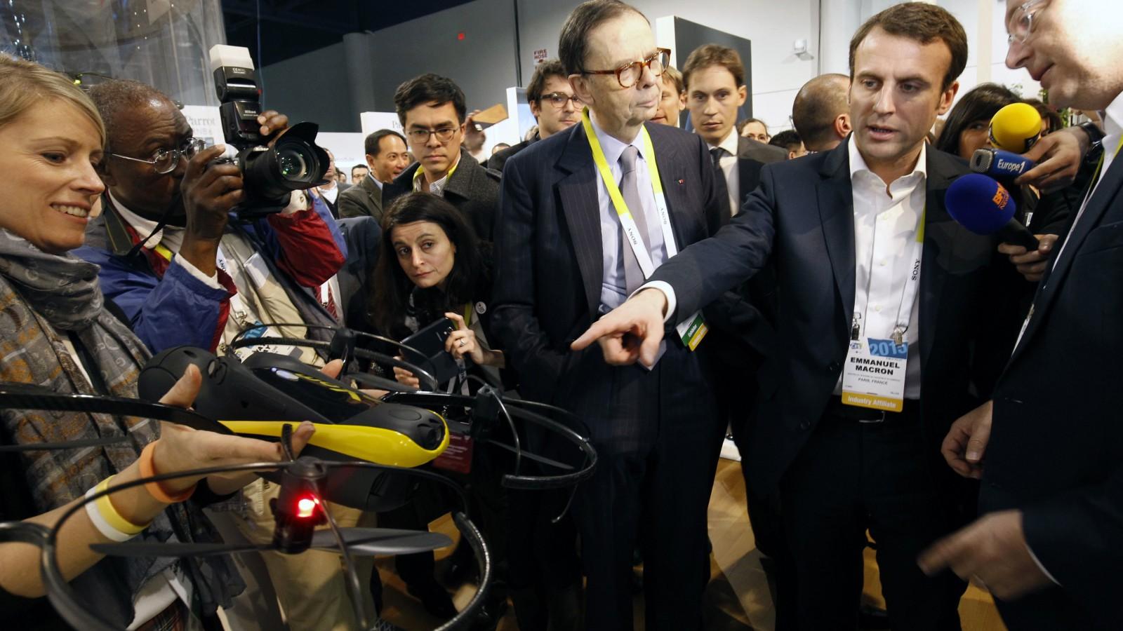France's Economy Minister Emmanuel Macron points to a Parrot Exom Sensefly drone.