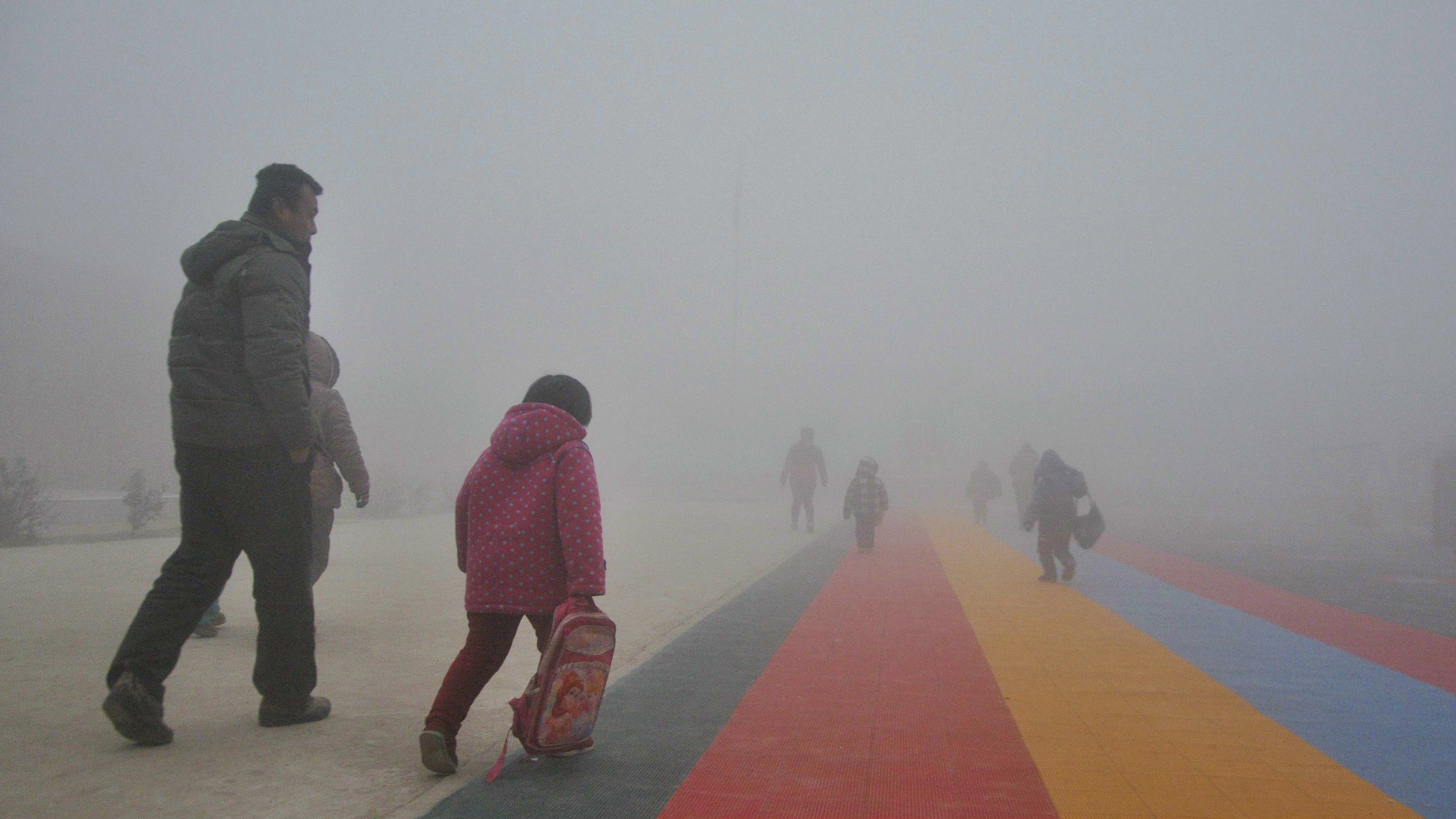 Parents walk primary school students to school amid thick haze in Chiping county, Shandong province January 16, 2015