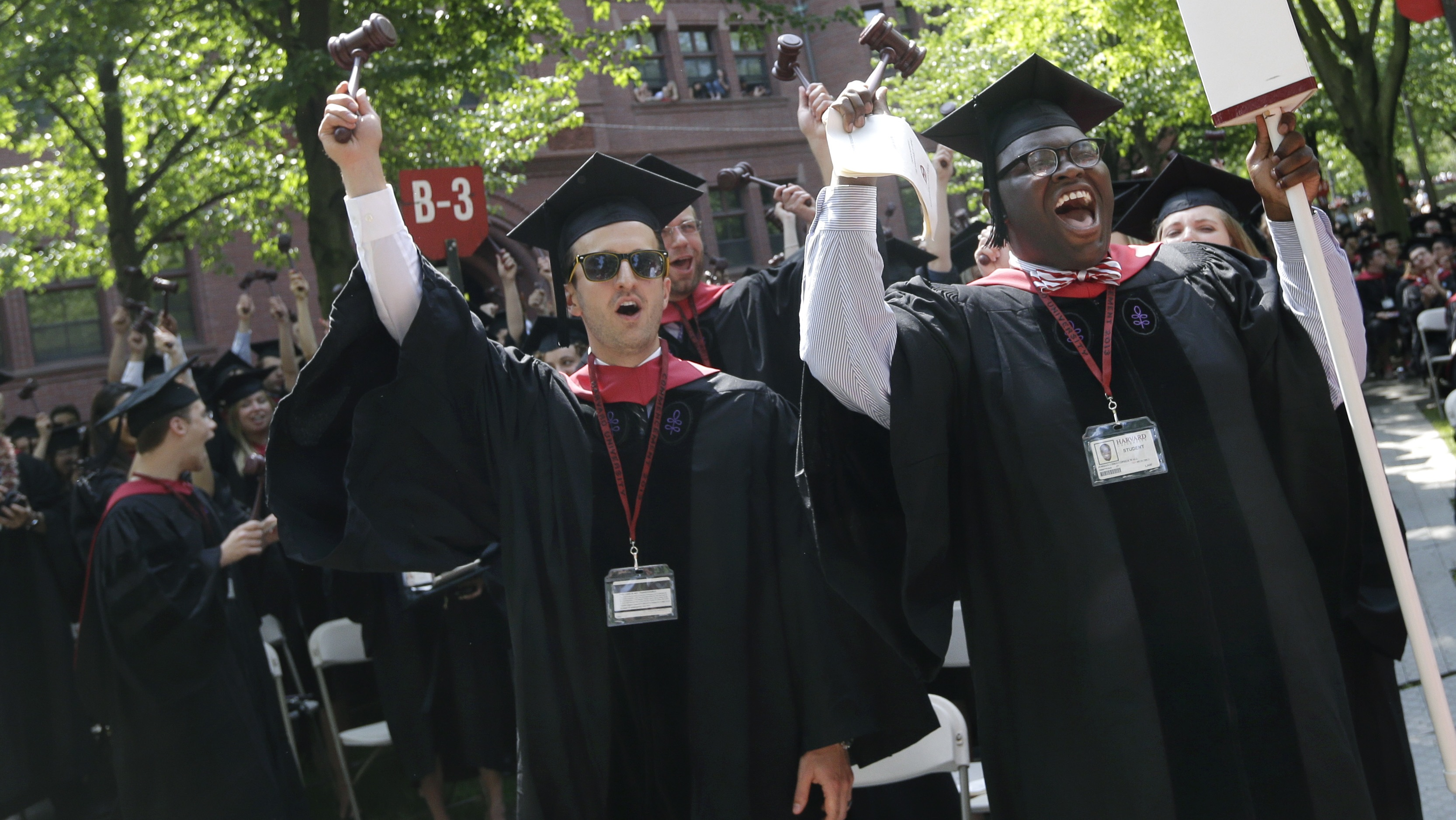 Adam Derry, left, and Jordan Christopher Wall, right, lead the cheers from students graduating from Harvard University's School of Law during commencement ceremonies in Cambridge, Mass., Thursday, May 30, 2013. (AP Photo/Elise Amendola)