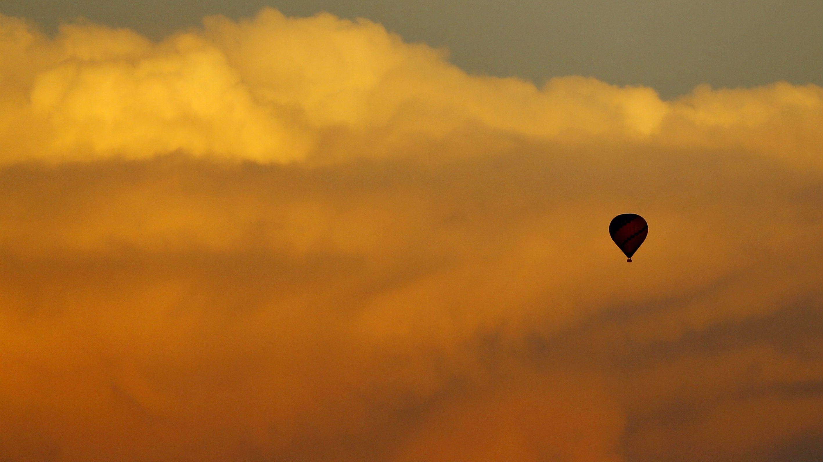 A hot air balloon floats past a distant thunderstorm after sunset near San Diego, California, August 15, 2014.