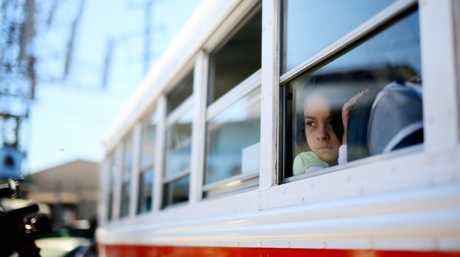 A young girl prepares to depart a bus with her parents before a protest at the U.S.-Mexico border during a Dream Act protest in Tijuana, Mexico, March 10, 2014. Approximately 40 protesters turned themselves in at the border in an attempt to get arrested trying to enter the United States, to bring light to deportations by the Obama administration. REUTERS/Sandy Huffaker (MEXICO - Tags: POLITICS SOCIETY EDUCATION CRIME LAW IMMIGRATION)
