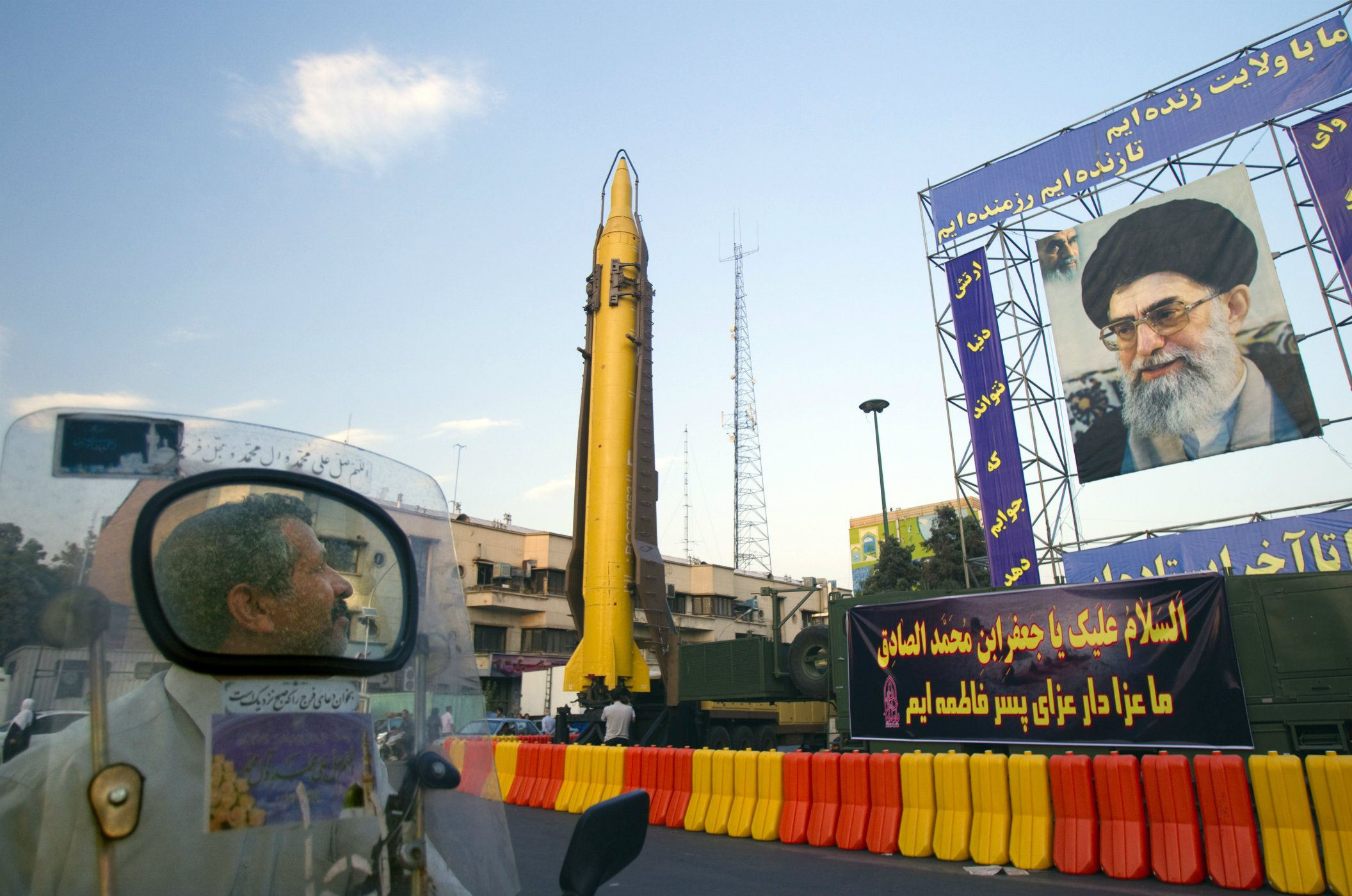 "A motorcyclist looks at an Iranian-made Ghadr-F missile during a war exhibition held by Iran's revolutionary guard to mark the anniversary of the Iran-Iraq war (1980-88), also known in Iran as the ""Holy Defence"", at Baharestan square near the Iranian Parliament in southern Tehran September 23, 2011. A portrait of Iran's Supreme Leader Ayatollah Ali Khamenei is seen on right. REUTERS/Morteza Nikoubazl"