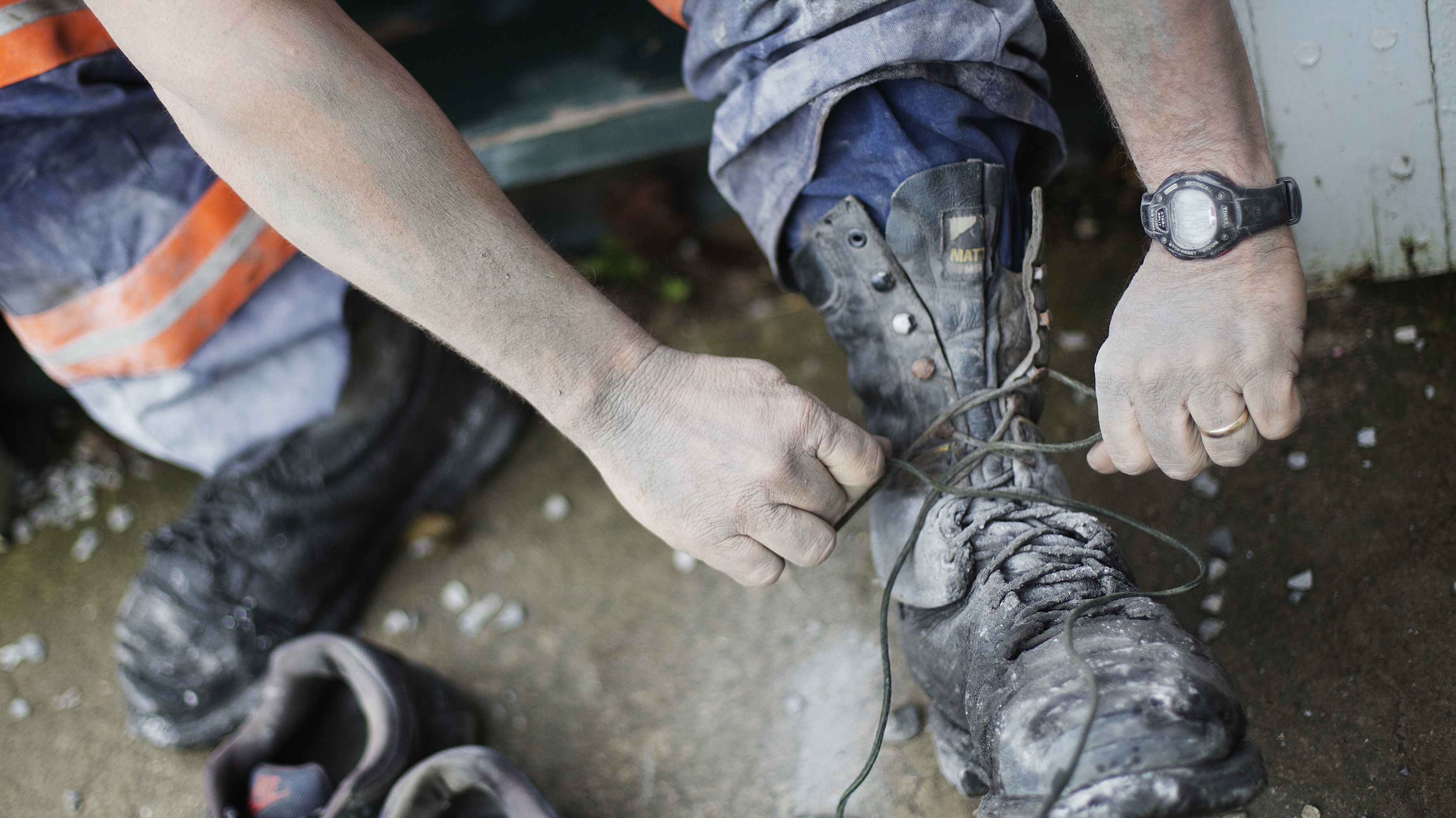 A Kentucky coal miner removes boots covered in toxic coal dust.