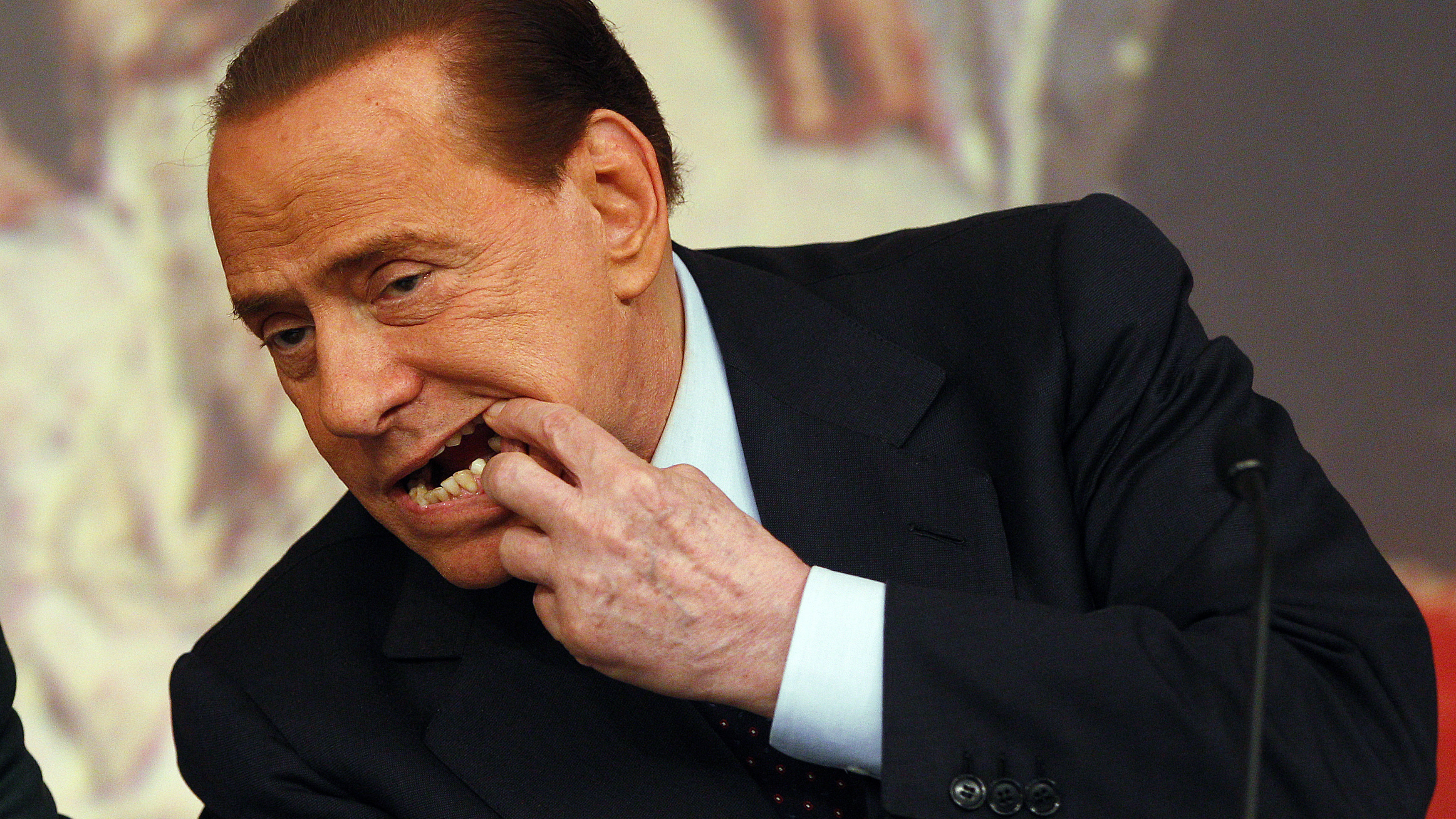 Italian Prime Minister Silvio Berlusconi shows his teeth during a news conference at Chigi palace in Rome February 9, 2011. Italy's government will request a parliamentary confidence vote on a package of measures to raise the taxation powers of town councils, Berlusconi said on Wednesday. REUTERS/Tony Gentile