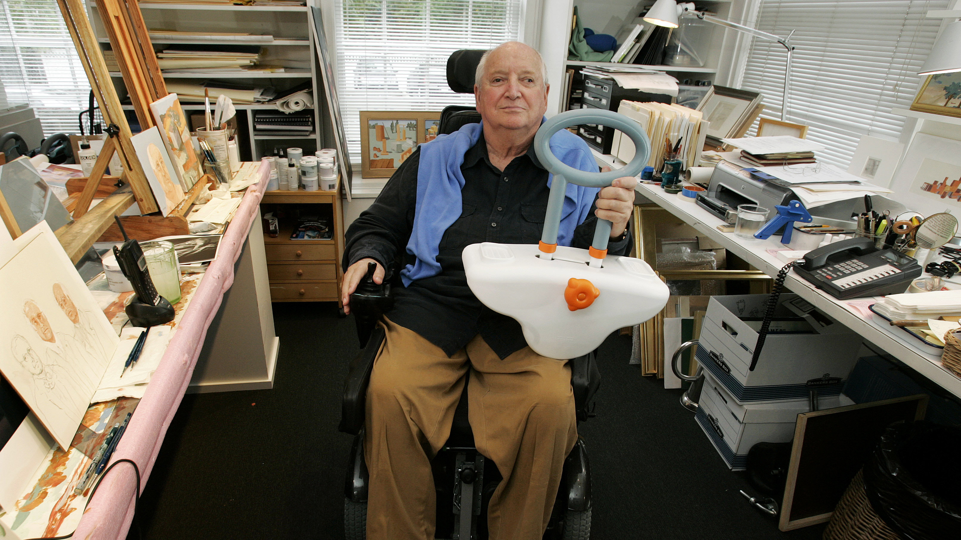 Architect and designer Michael Graves sits in his studio Friday, Sept. 11, 2009, in Princeton, N.J., as he holds a bathtub handle he designed to help the handicapped and elderly.