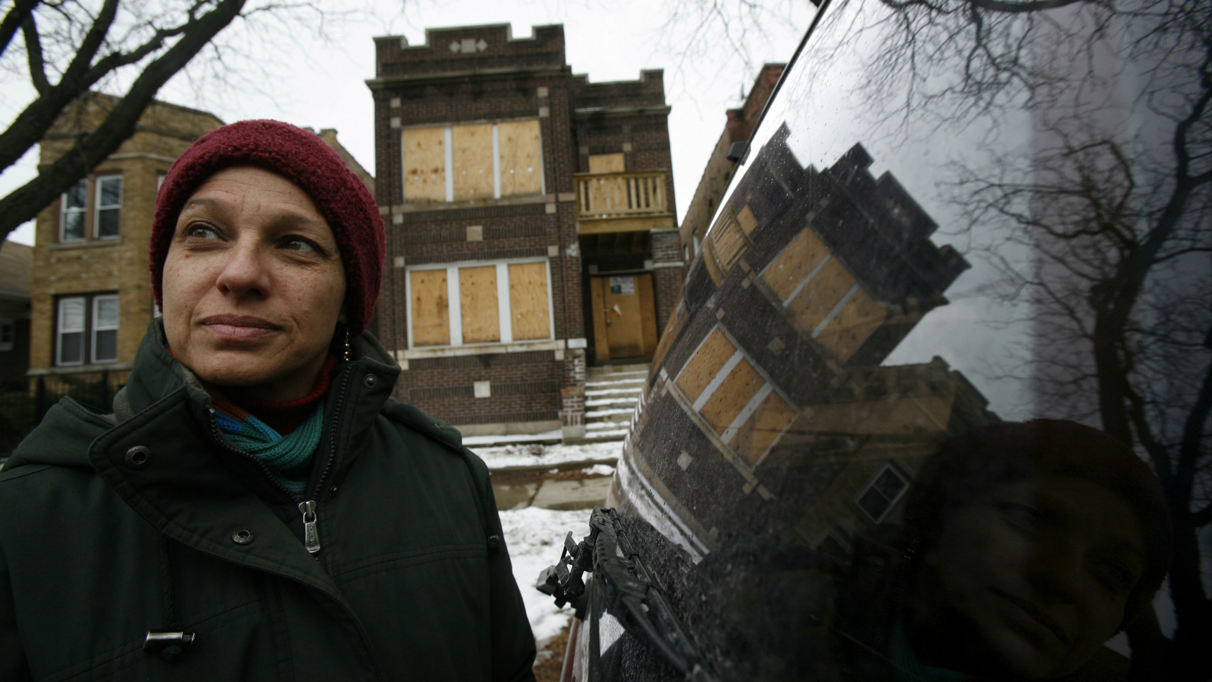 """Greater Southwest Development Corporation Director of Counseling Services Livia Villareal stands before a foreclosed home in Chicago January 28, 2008. No matter who wins the U.S. presidential election in November, their """"to do"""" list will probably include urban renewal. For while the subprime crisis may force the U.S. economy into recession, it has already brought boarded-up homes and broken dreams to thousands of minority families inner cities. TO MATCH FEATURE USA-HOUSING/MINORITIES REUTERS/John Gress (UNITED STATES)"""