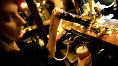 A barmaid pulls a pint at a pub in central London.