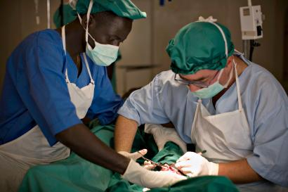 Surgeon Jose Sanchez (R) from Spain operates on a soldier