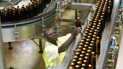 A worker inspects beer bottles on a conveyor belt of a factory in Nairobi, Kenya.
