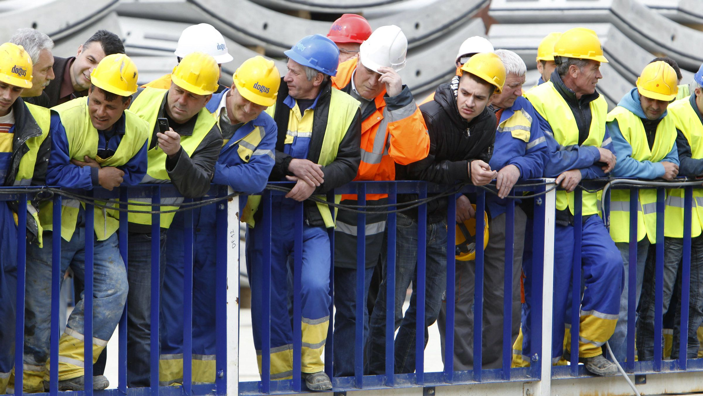 Workers look at the new drilling machine at a construction site of Sofia's metropolitan.
