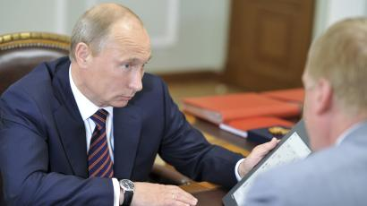 Russian Prime Minister Vladimir Putin (L) holds a prototype of a tablet computer during his meeting with Anatoly Chubais, head of technology conglomerate Rosnano, at the Novo-Ogaryovo residence near Moscow August 18, 2011. The Russian state company plans to start mass production next year of cheap plastic-based tablet computers for school students which it says will rival Apple Inc's iPad. REUTERS/Alexei Nikolsky/RIA Novosti/Pool