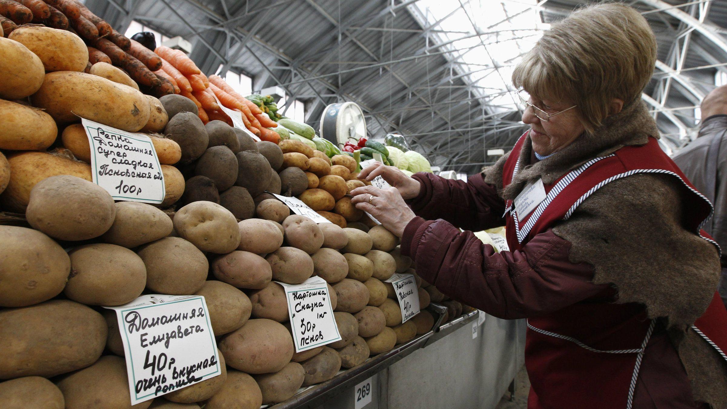 A vendor sells potatoes at the city market in St. Petersburg.