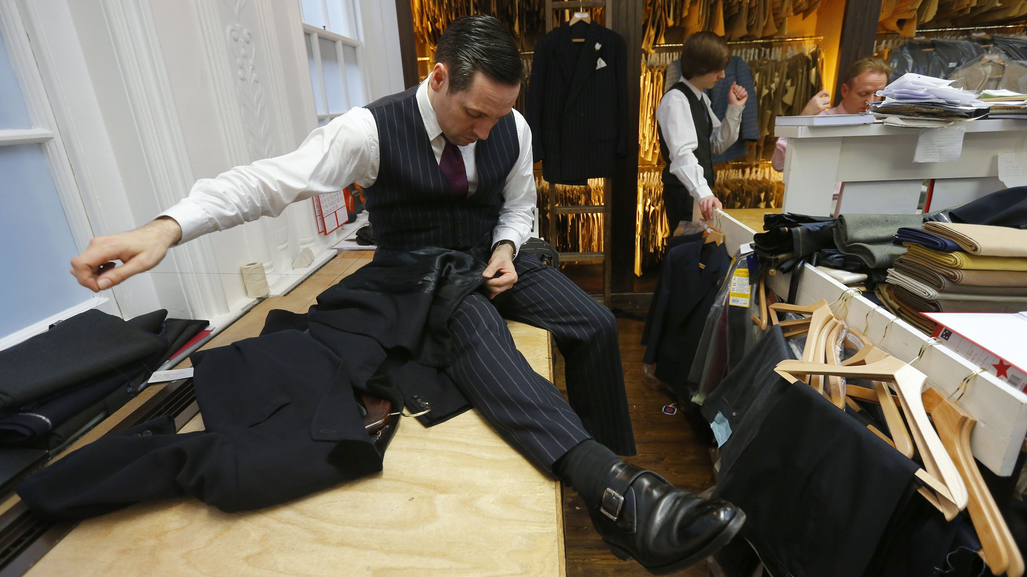 A tailor works on a bespoke men's suit.