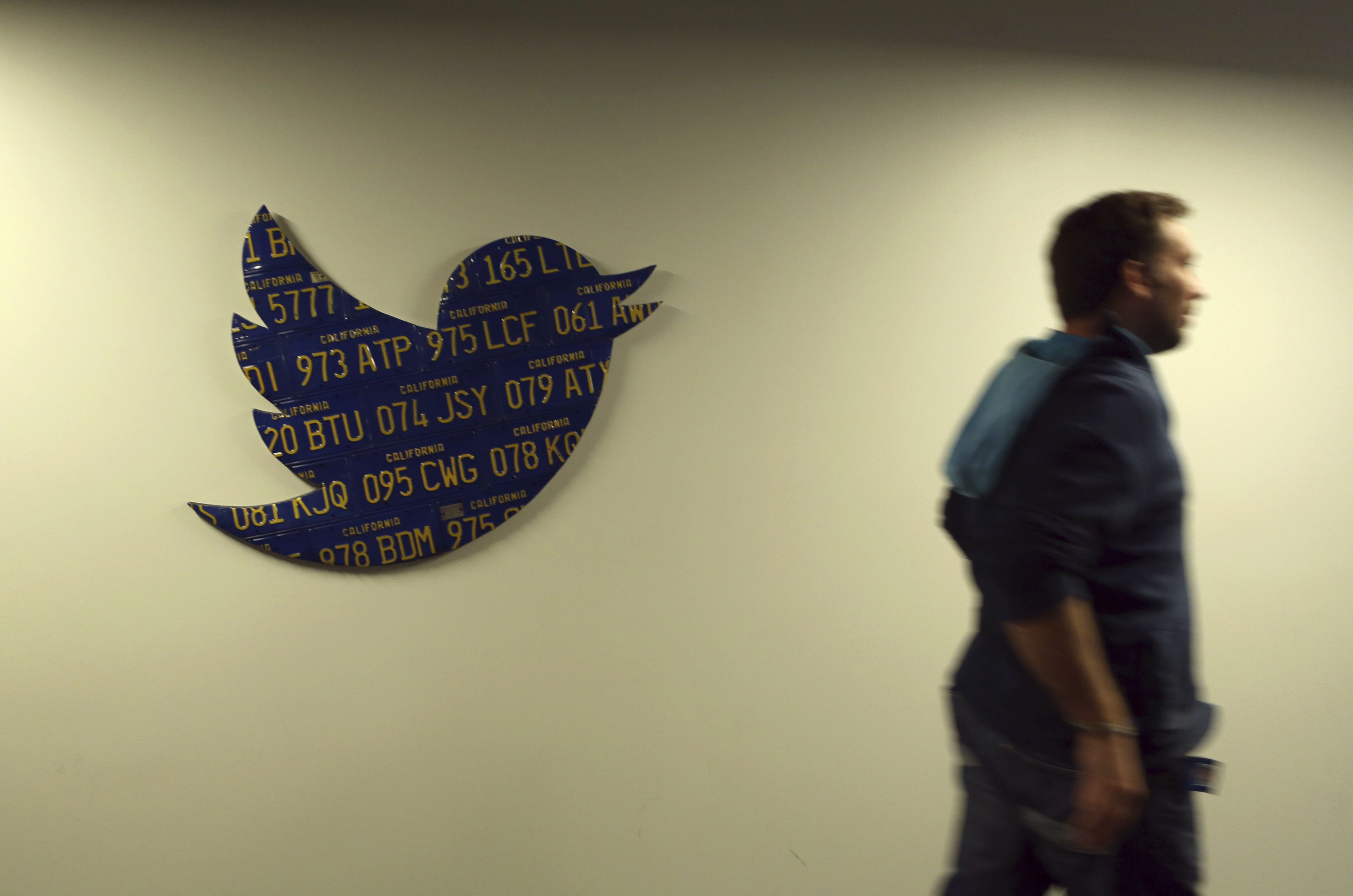 An employee walks past a Twitter logo made from Californian license plates at the company's headquarters in San Francisco, California October 4, 2013. Twitter Inc, racing toward the largest Silicon Valley IPO since Facebook Inc's 2012 coming-out party, hopes to woo investors with rip-roaring revenue growth despite having posted big losses over the past three years. The eight-year-old online messaging service gave potential investors their first glance at its financials on Thursday when it publicly filed its IPO documents, setting the stage for one of the most-anticipated debuts in over a year.