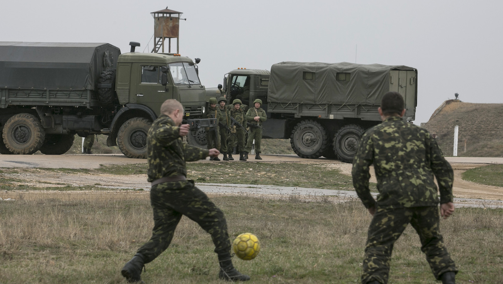 Russian soldiers watch Ukrainian servicemen play soccer at Belbek airport in the Crimea region March 4, 2014. A column of unarmed Ukrainian servicemen arrived at the base for negotiations with Russian troops on Tuesday, local media reported.  REUTERS/Baz Ratner (UKRAINE - Tags: MILITARY POLITICS SPORT SOCCER TPX IMAGES OF THE DAY) - RTR3G10A