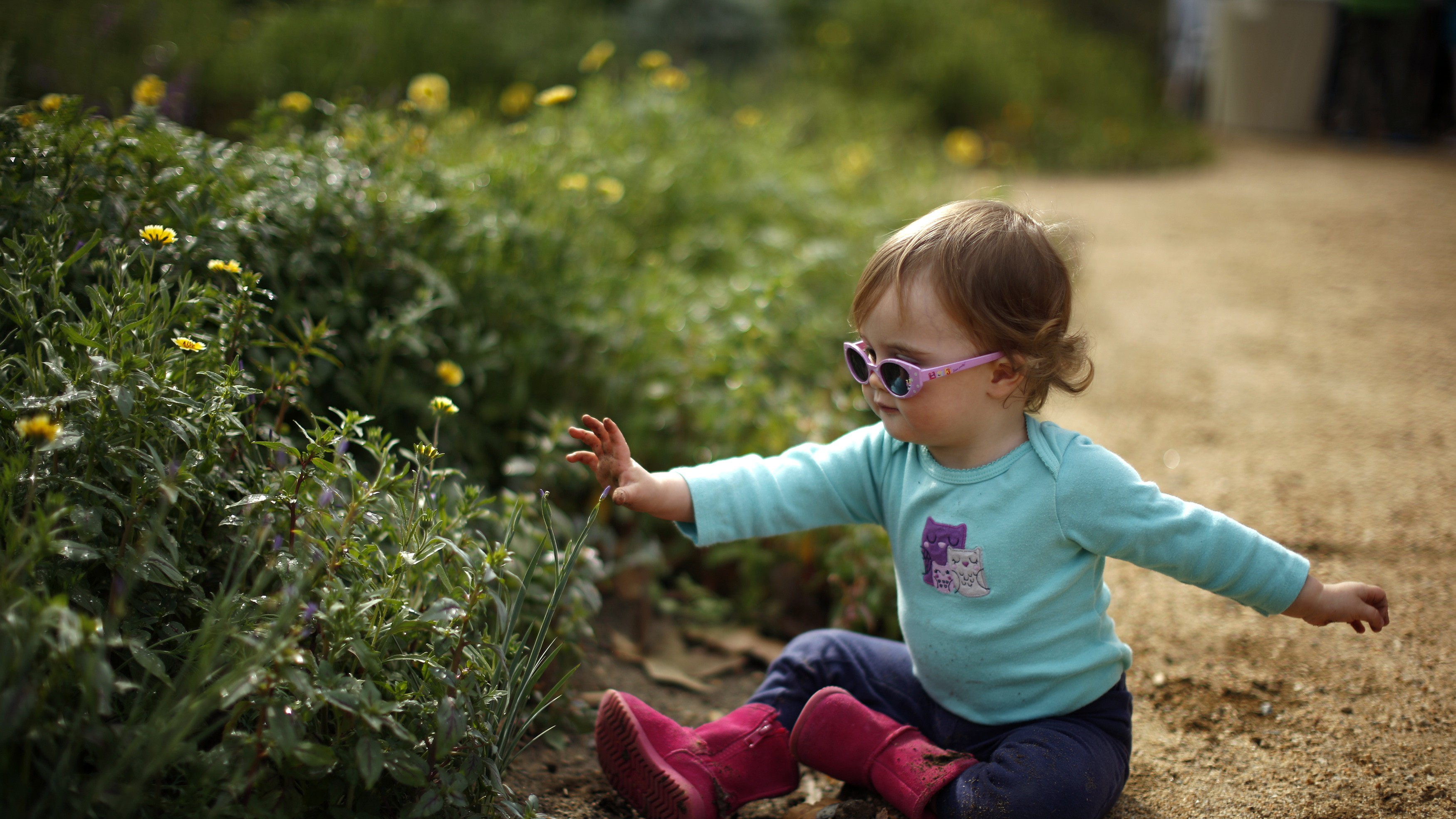 Fifteen-month-old Amelia Tompkins plays in the Pollinator Garden at the Natural History Museum in Los Angeles, California March 20, 2014. Spring officially began on Thursday in the northern hemisphere, and is known as both the spring or vernal equinox. REUTERS/Lucy Nicholson (UNITED STATES - Tags: SOCIETY TRAVEL ENVIRONMENT) - RTR3HYJY