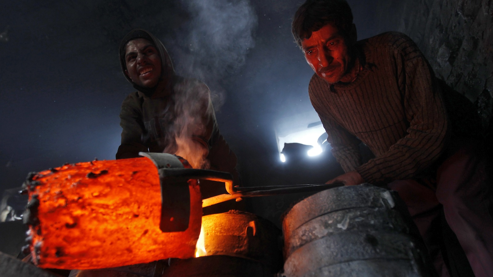Workers pour melted copper in a mould to make utensils and accessories inside a workshop in Srinagar March 27, 2014. REUTERS/Danish Ismail