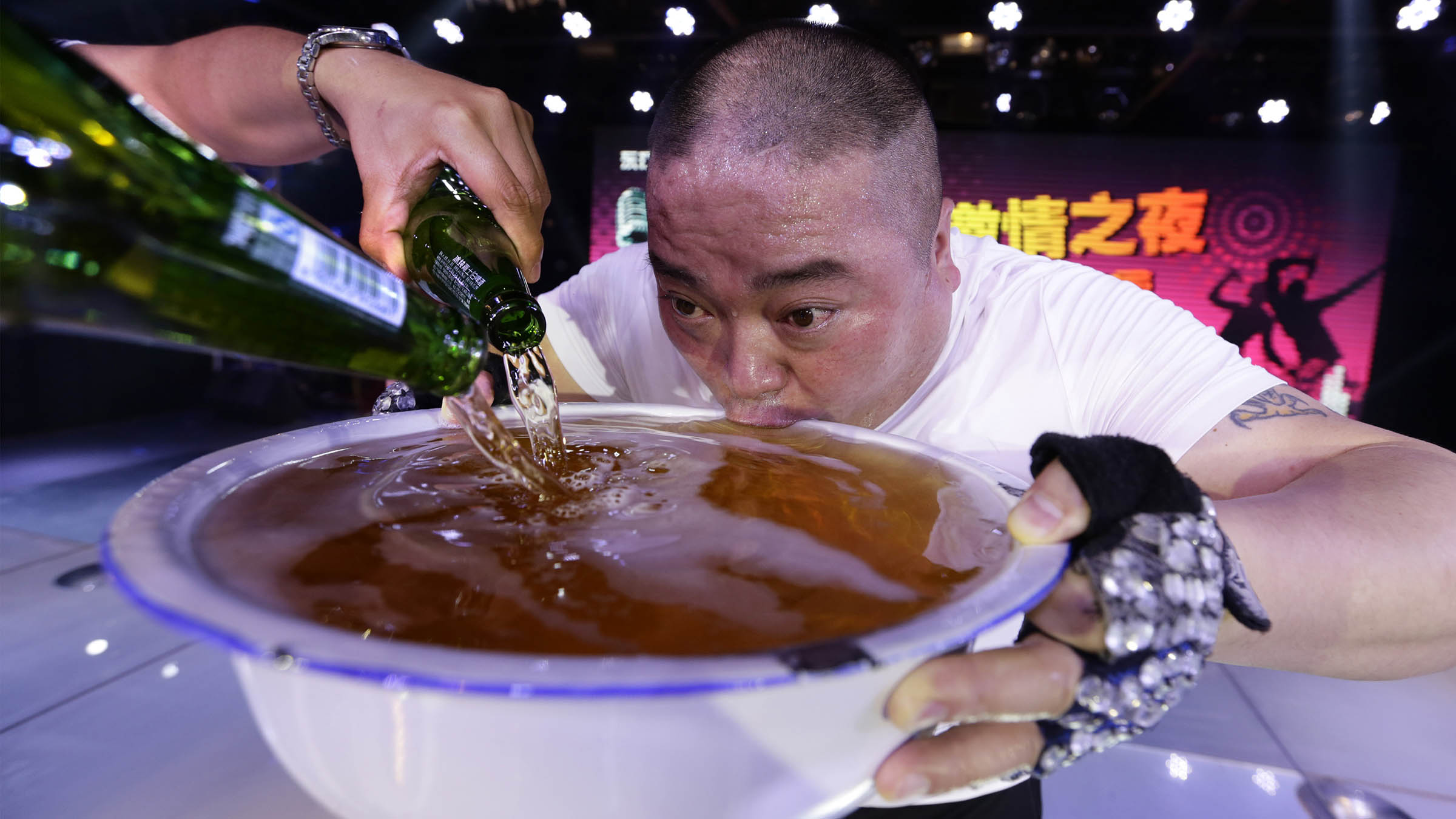 A singer drinks from a huge bowl of beer on-stage as he pays tribute to the customers after performing at an entertainment club in Beijing May 8, 2014. Picture taken May 8, 2014. REUTERS/Jason Lee (CHINA - Tags: SOCIETY TPX IMAGES OF THE DAY) - RTR3ODZ2