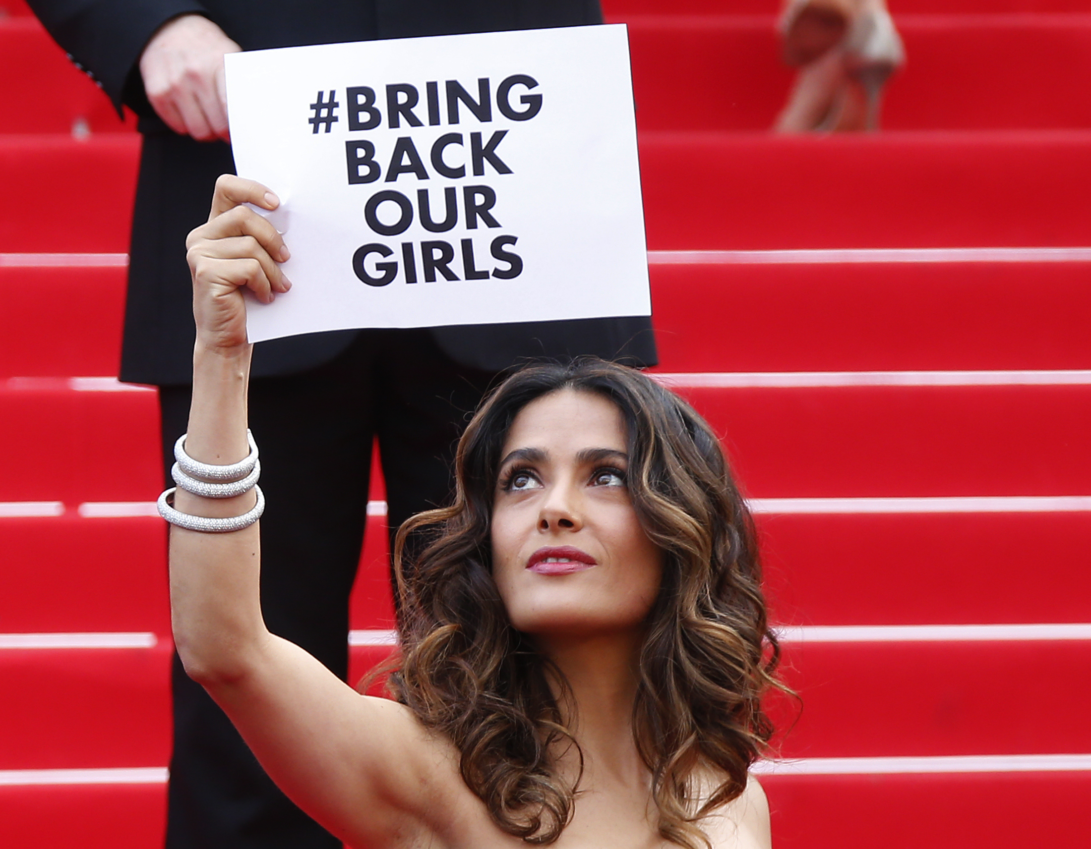 Actress and producer Salma Hayek holds a placard