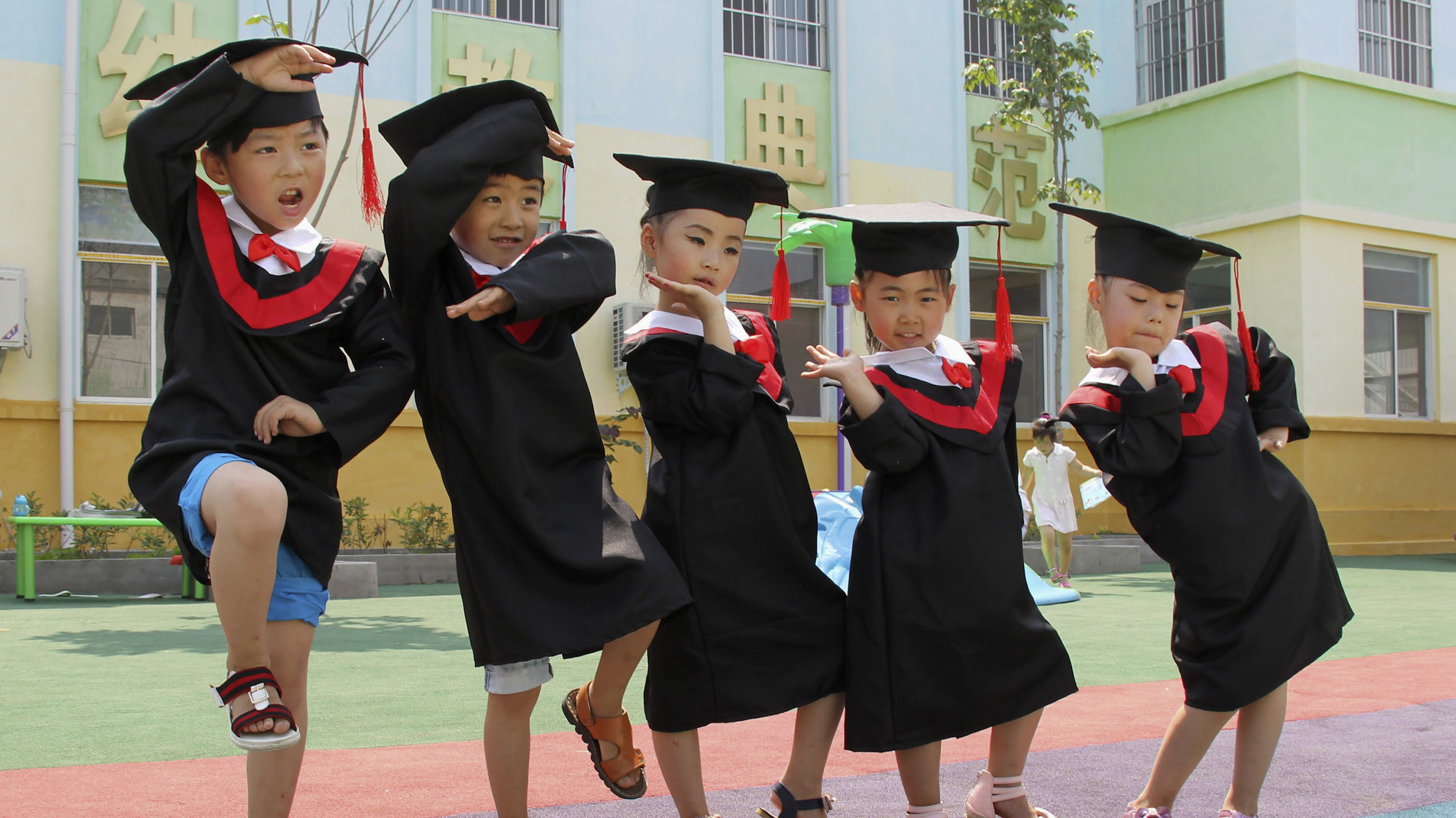 Children in gowns and mortarboards pose for pictures during their kindergarten graduation ceremony.