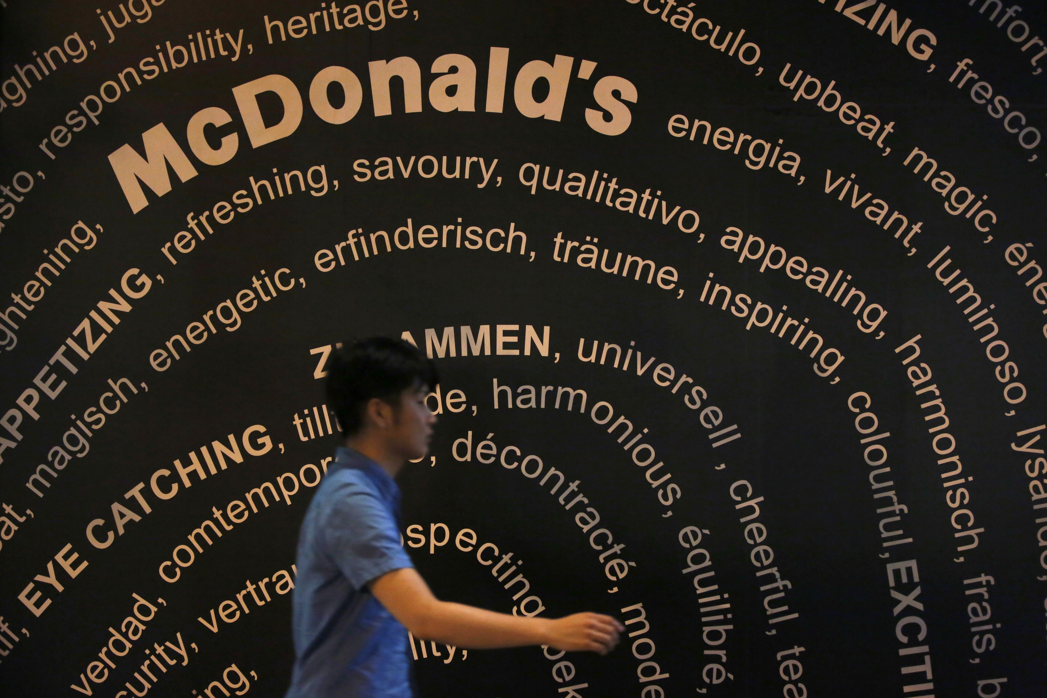 A passerby walks past a McDonald's store in Tokyo July 31, 2014. Officials from McDonald's in China and Hong Kong have not responded to requests for information on the impact on sales from the scandal, but McDonald's Holdings Co (Japan) Ltd on Tuesday scrapped its full-year earnings guidance after the China scare forced it to switch to alternative chicken supplies. A McDonald's Japan executive said sales had dropped 15-20 percent on a daily basis due to the scare. REUTERS/Issei Kato (JAPAN - Tags: BUSINESS EMPLOYMENT FOOD HEALTH) - RTR40RV4