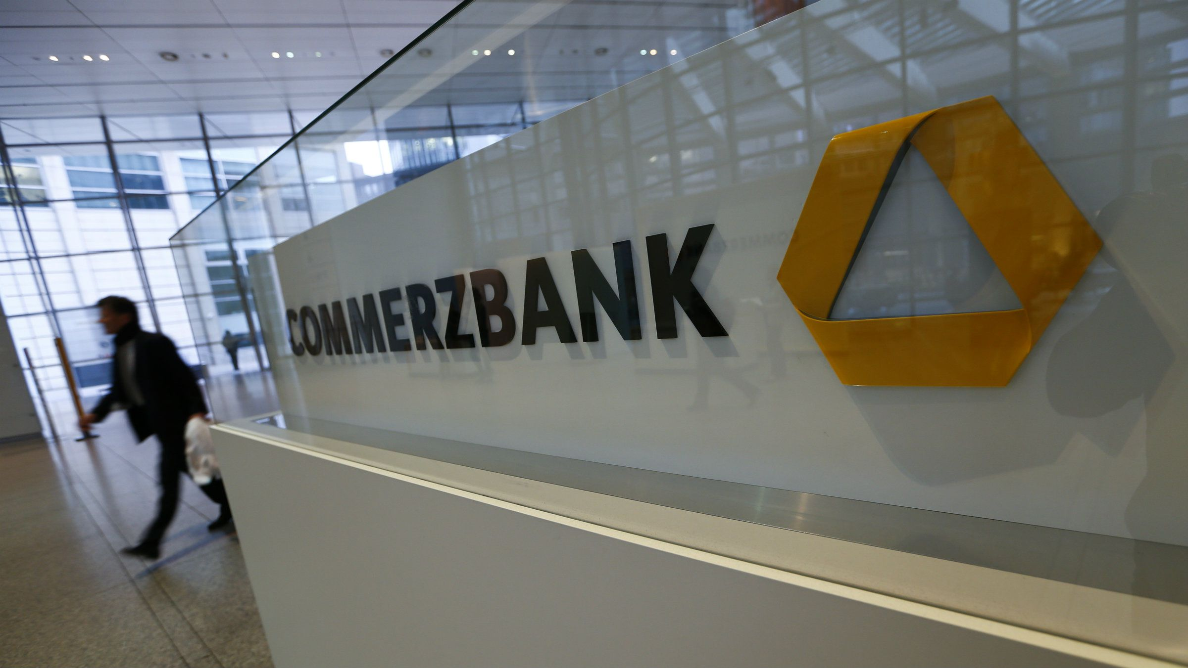 A man walks past a logo of Commerzbank ahead of the bank's annual news conference in Frankfurt.